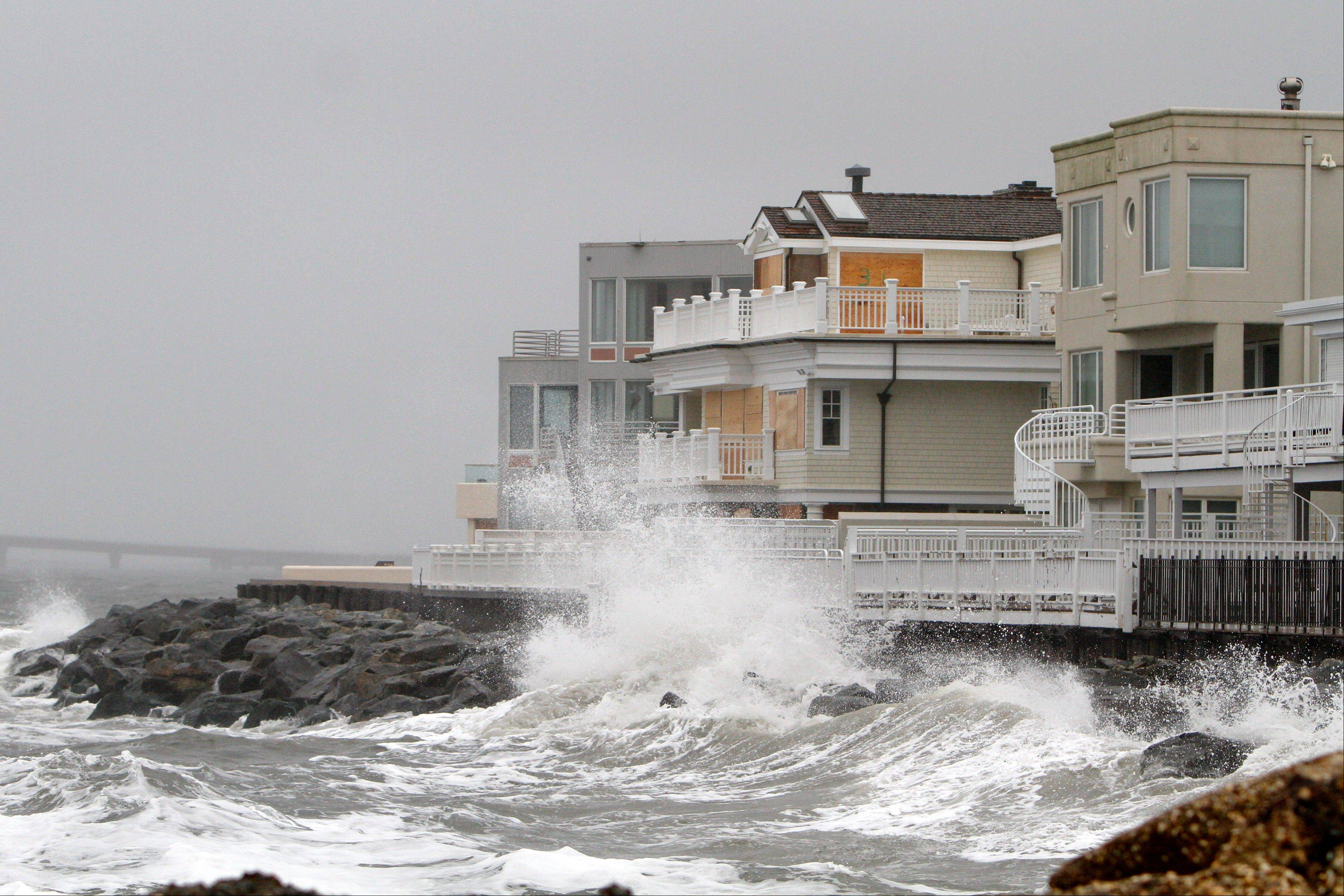 Waves crash onto the sea wall protecting homes in Longport, N.J., Sunday, as Hurricane Sandy approaches the area.