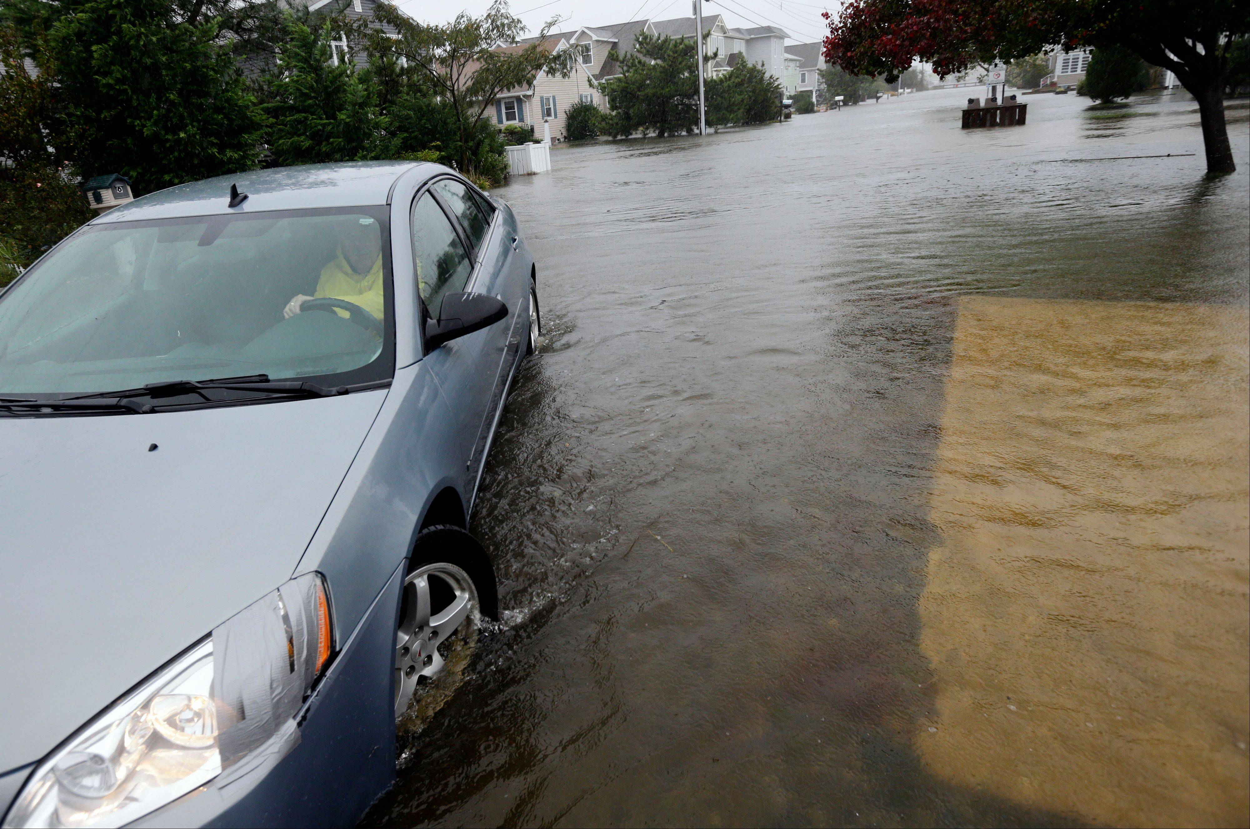 Richard Thomas moves a neighbors' car out of the rising water as Hurricane Sandy bears down on the East Coast in Fenwick Island, Del.