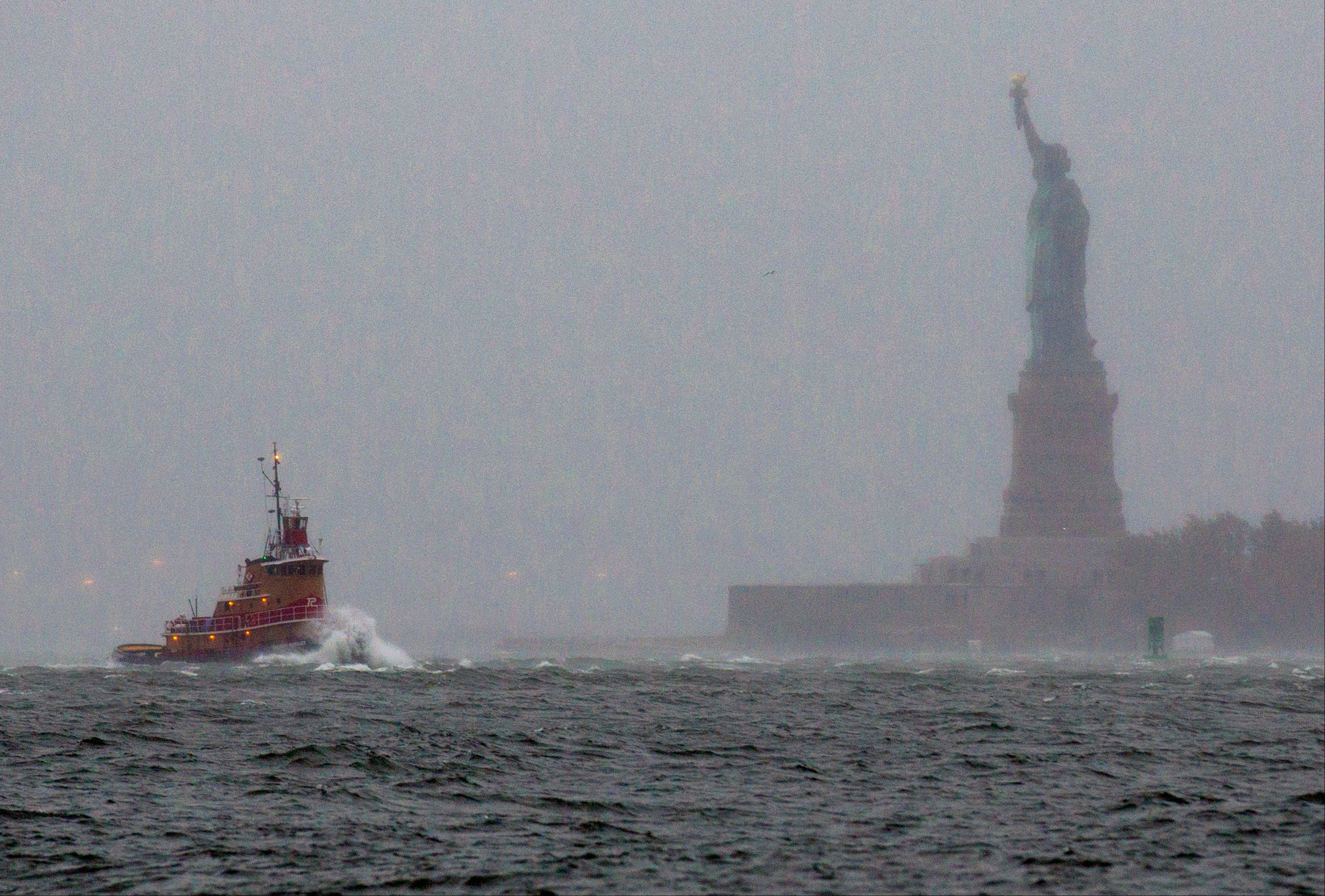 Waves crash over the bow of a tug boat as it passes near the Statue of Liberty in New York Monday as rough water as the result of Hurricane Sandy churned the waters of New York Harbor.