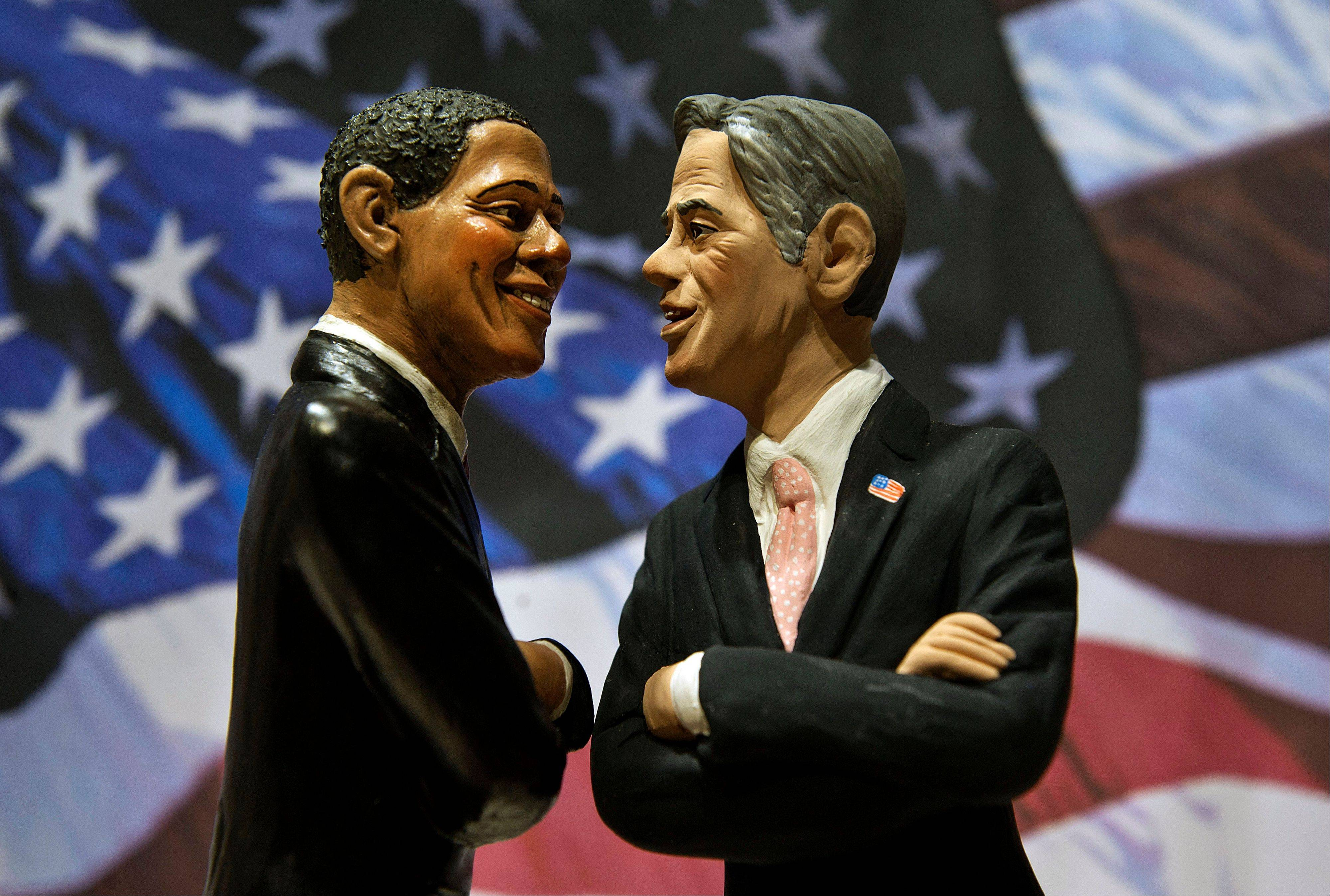 Statuettes depicting President Barack Obama, left, and Republican rival Mitt Romney are backdropped by the Stars and Stripes in a shop in Naples, Italy. Interest in the U.S. presidential election is high around the world.