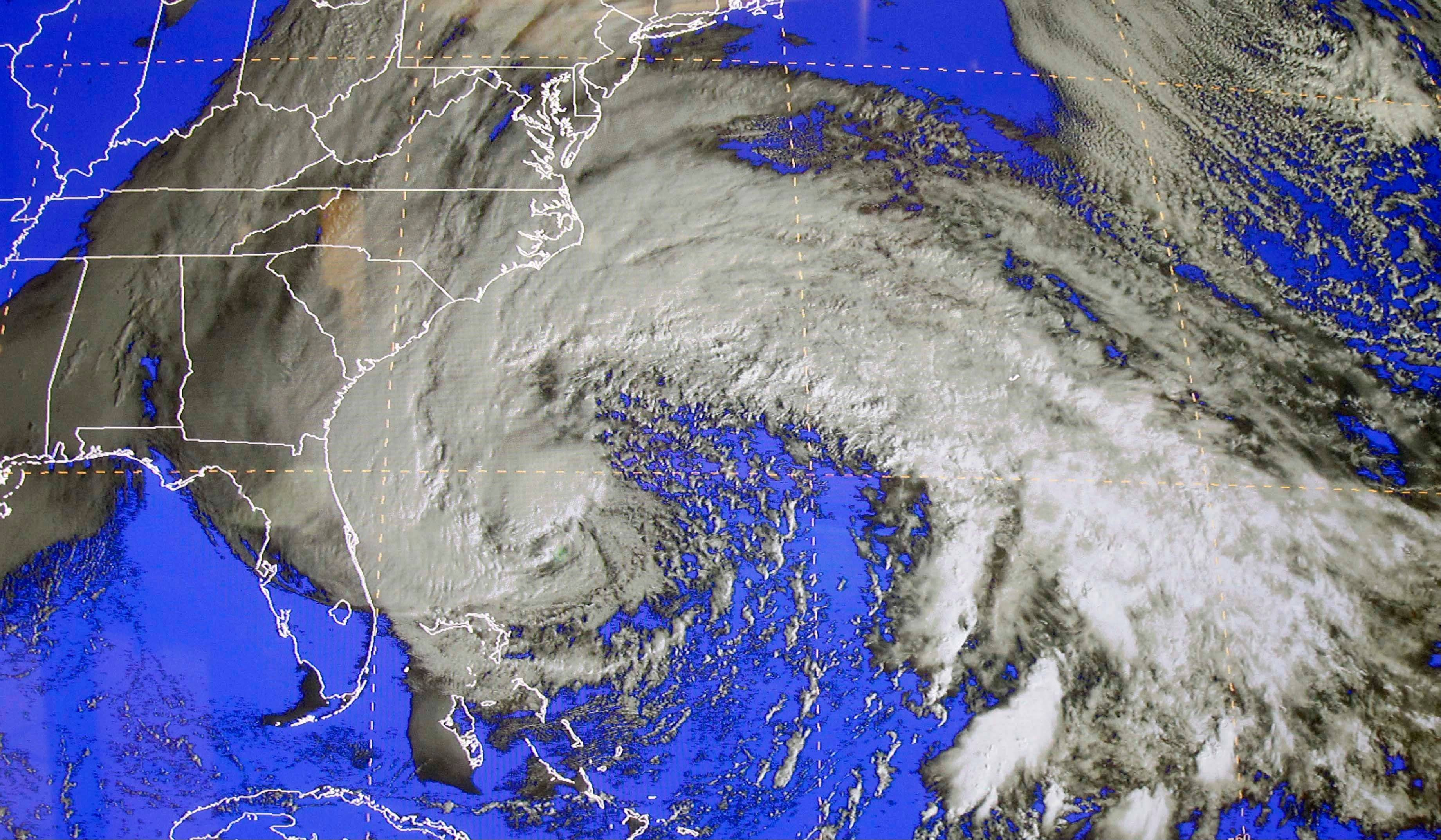 A satellite image of Sandy on Saturday at the National Hurricane Center in Miami. Early Saturday, the storm was about 335 miles southeast of Charleston, S.C. Tropical storm warnings were issued for parts of Florida's East Coast, along with parts of coastal North and South Carolina and the Bahamas. Tropical storm watches were issued for coastal Georgia and parts of South Carolina, along with parts of Florida and Bermuda. Sandy is projected to hit the Atlantic Coast early Tuesday.