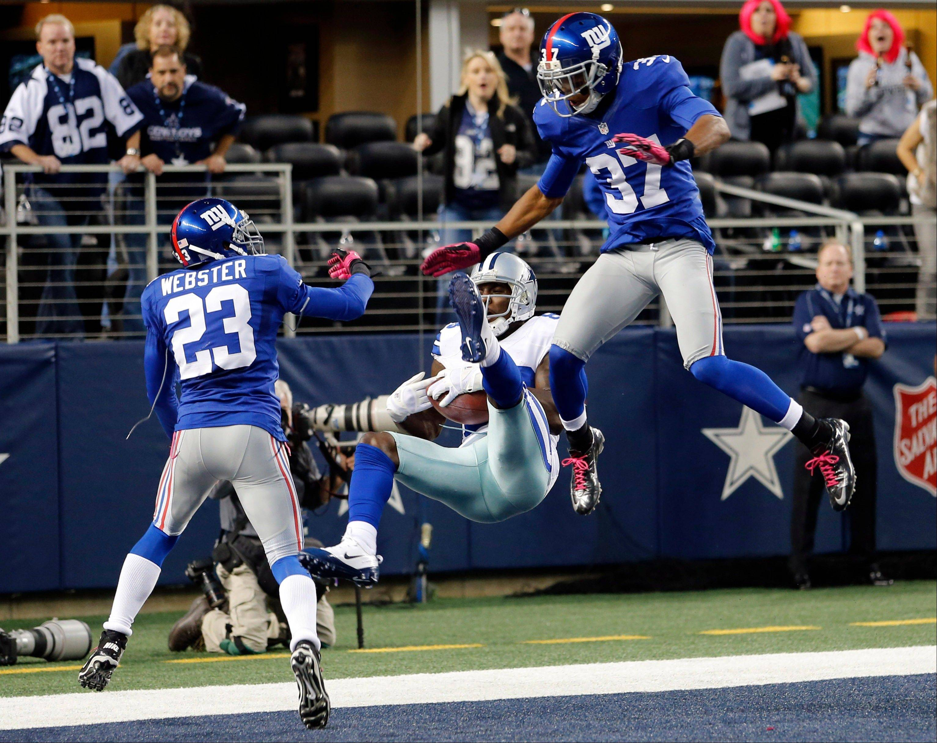 Dallas Cowboys wide receiver Dez Bryant (88) makes a last-minute reception between New York Giants cornerbacks Corey Webster (23) and Michael Coe (37) for a touchdown that was nullified after review.