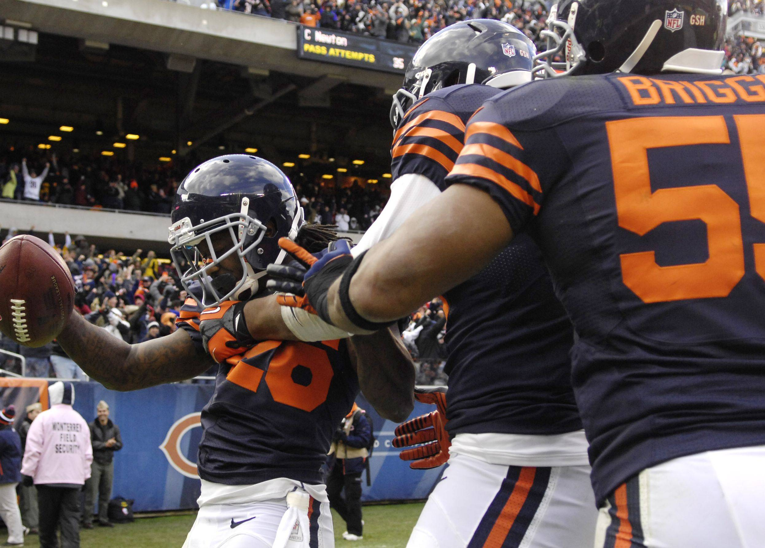 Bears cornerback Tim Jennings (26) is swarmed by teammates after his fourth-quarter interception return for a touchdown Sunday at Soldier Field. Jennings' play gave the Bears a 20-19 lead with 6:44 left in the game.