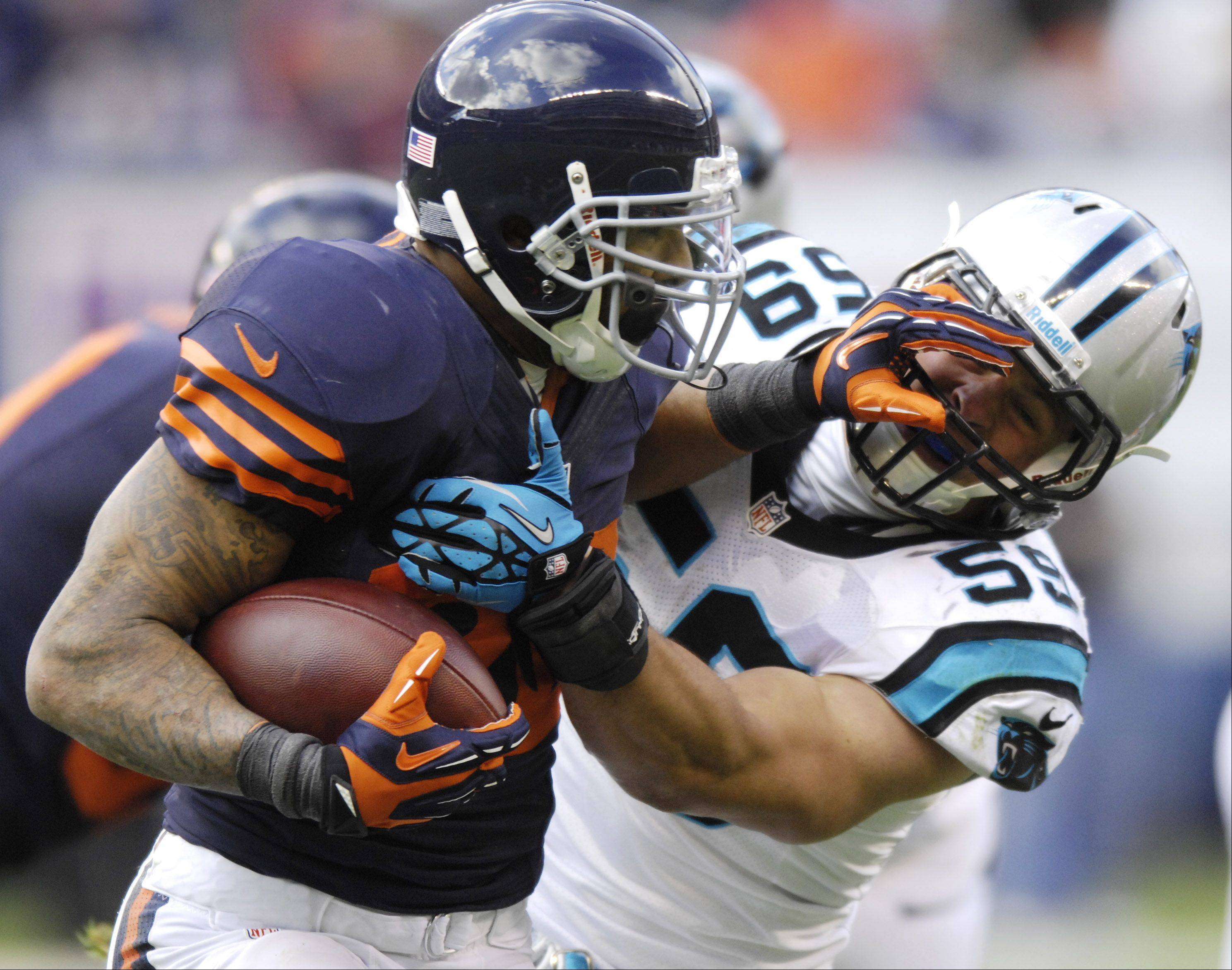 Chicago Bears running back Matt Forte fights off Carolina Panthers outside linebacker Luke Kuechly during Sunday's game at Soldier Field.