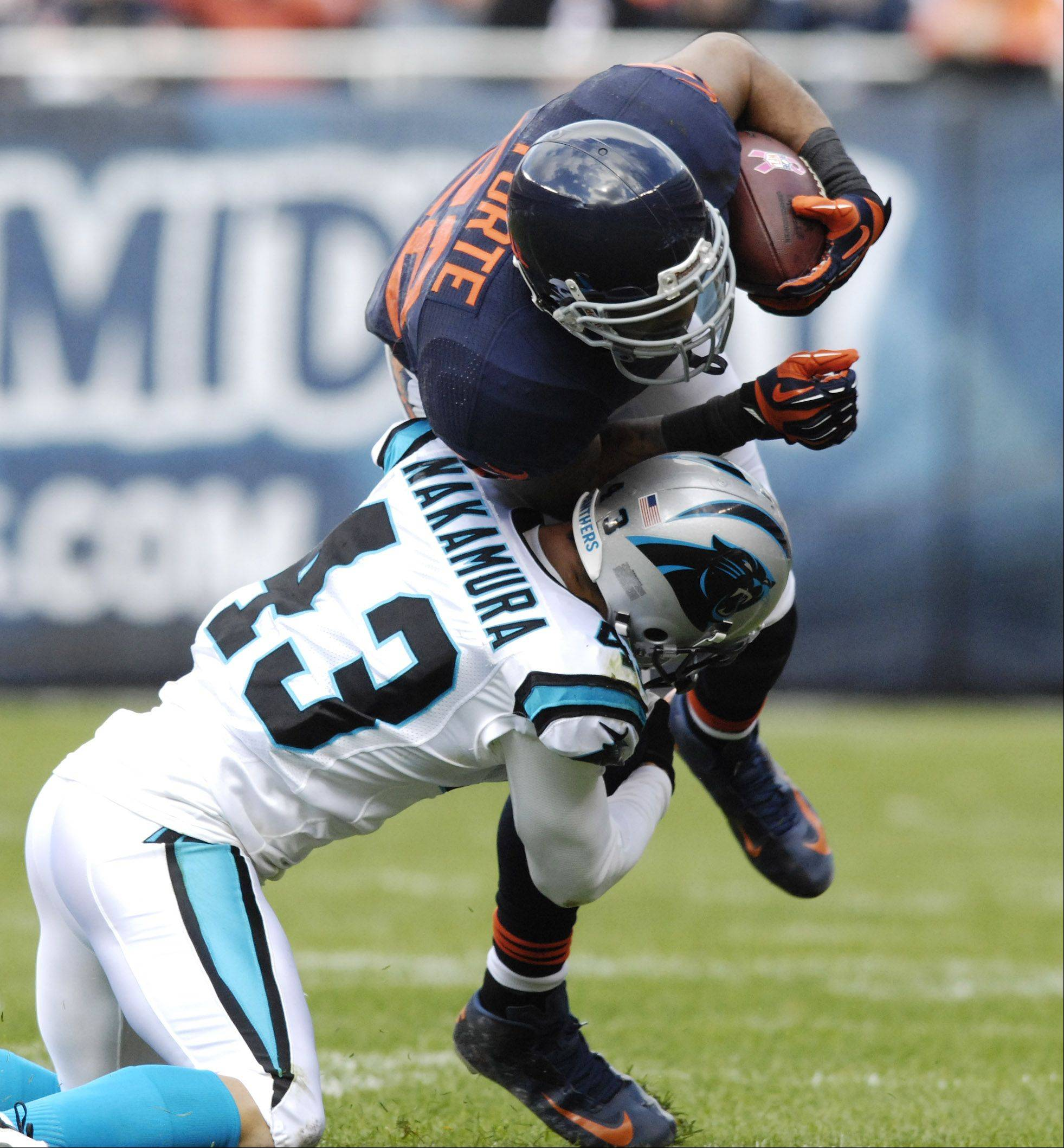Chicago Bears running back Matt Forte is tackled by Carolina Panthers free safety Haruki Nakamura during Sunday's game at Soldier Field.