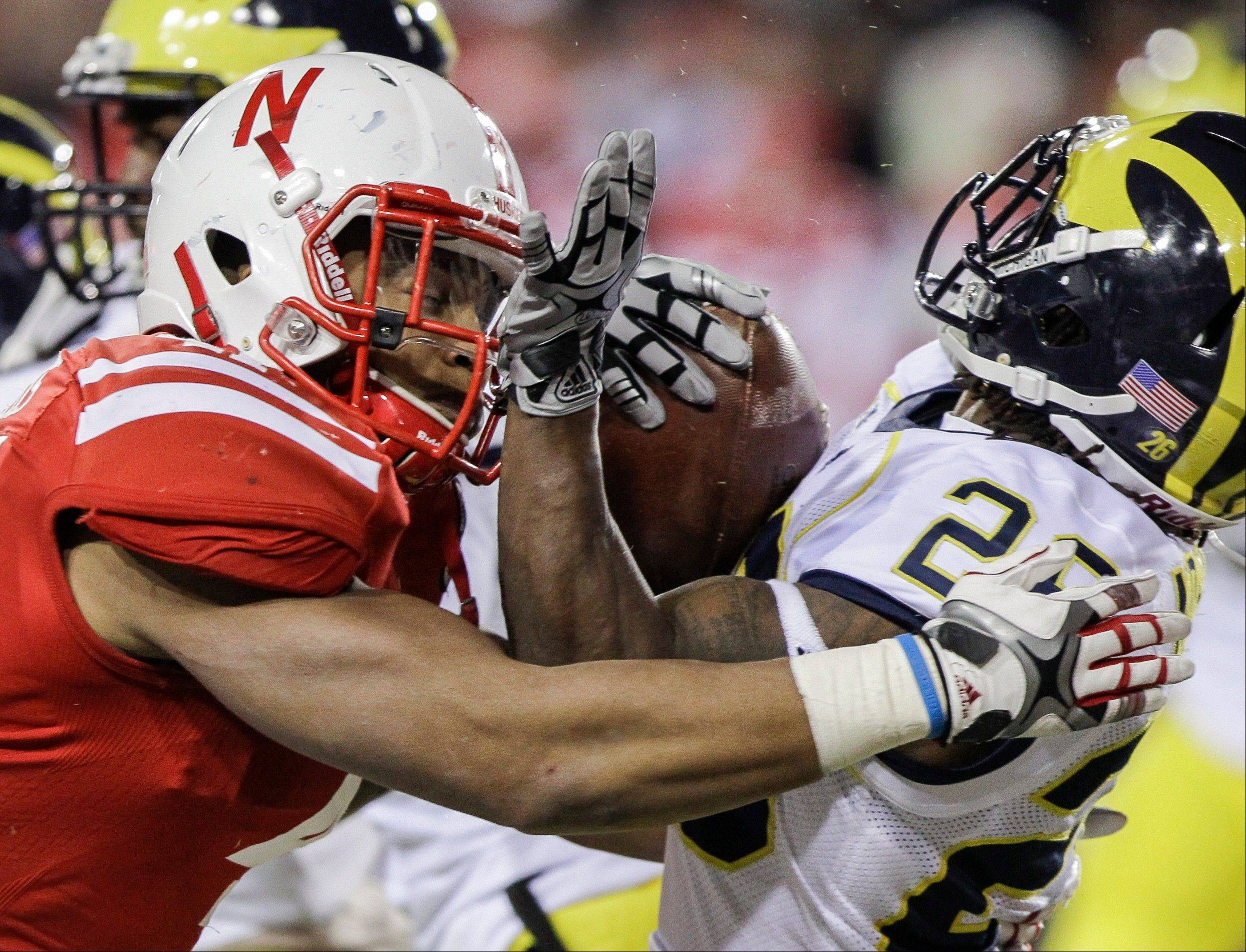 Michigan's Kenny Demens, right, is tackled by Nebraska's David Santos in the second half of an NCAA college football game in Lincoln, Neb., Saturday.
