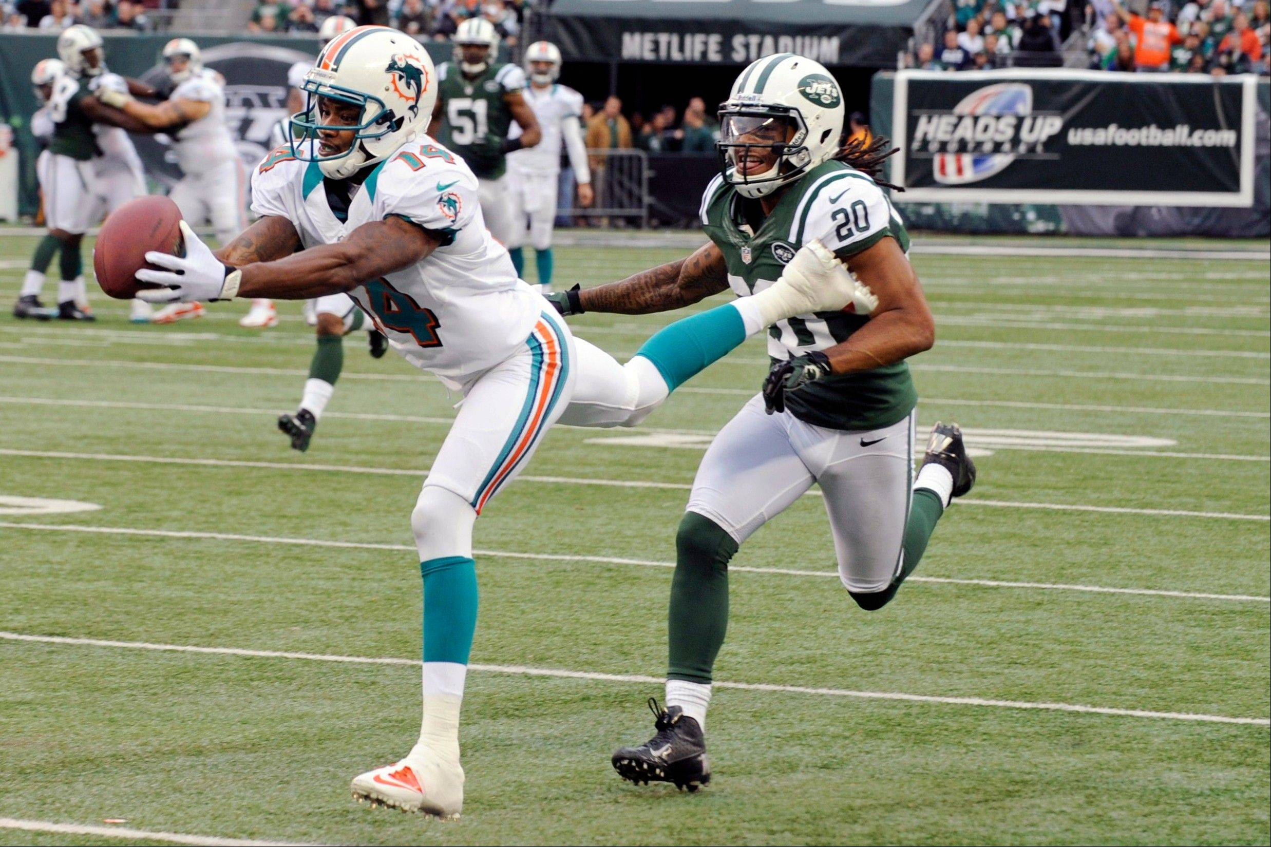 Miami Dolphins wide receiver Marlon Moore (14) catches a pass for a first down in front of New York Jets cornerback Kyle Wilson (20) during the first half in East Rutherford, N.J.