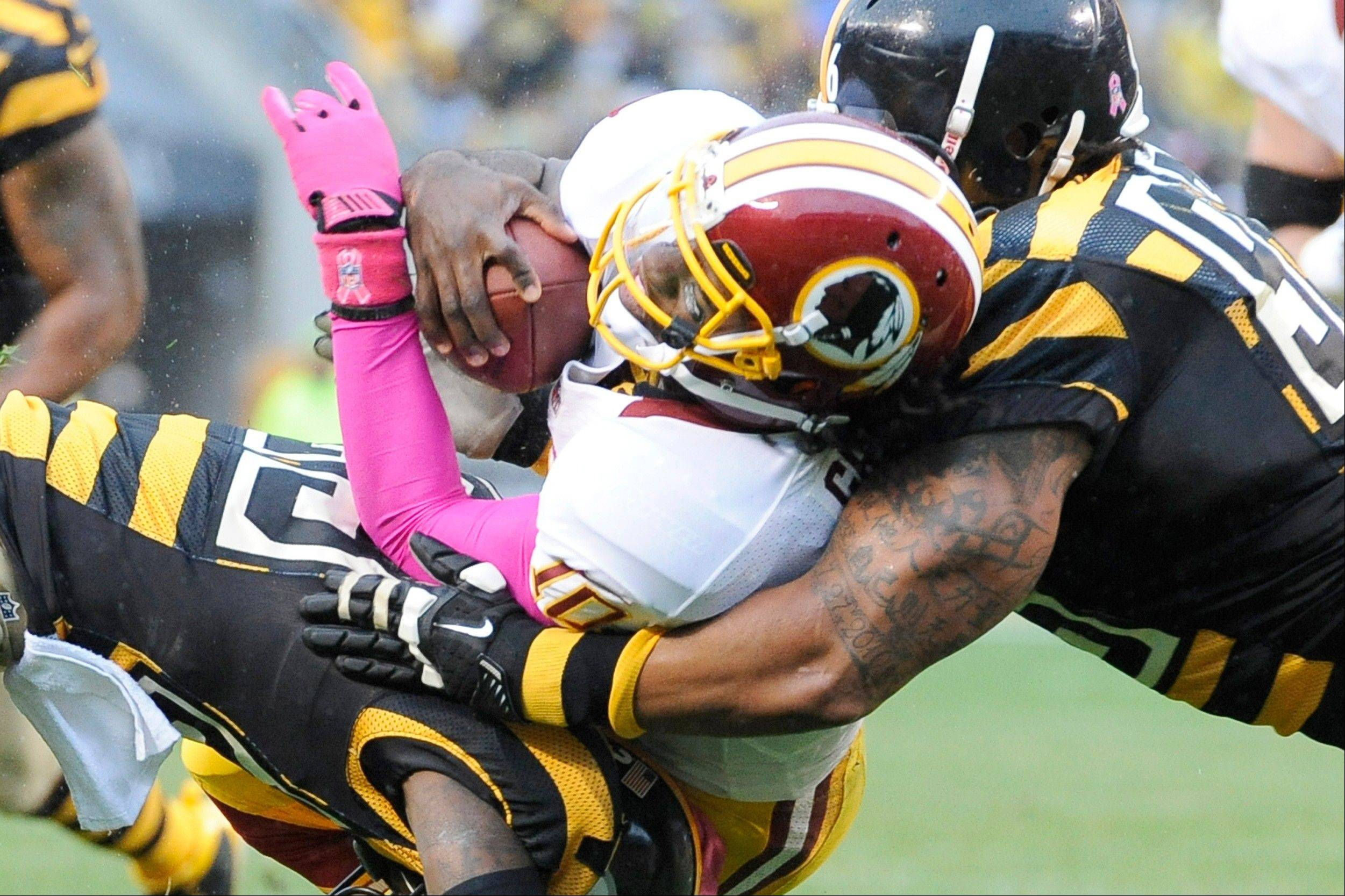 Washington Redskins quarterback Robert Griffin III, center, is stopped by Pittsburgh Steelers nose tackle Casey Hampton, right, and cornerback Keenan Lewis (23) in the second quarter in Pittsburgh.