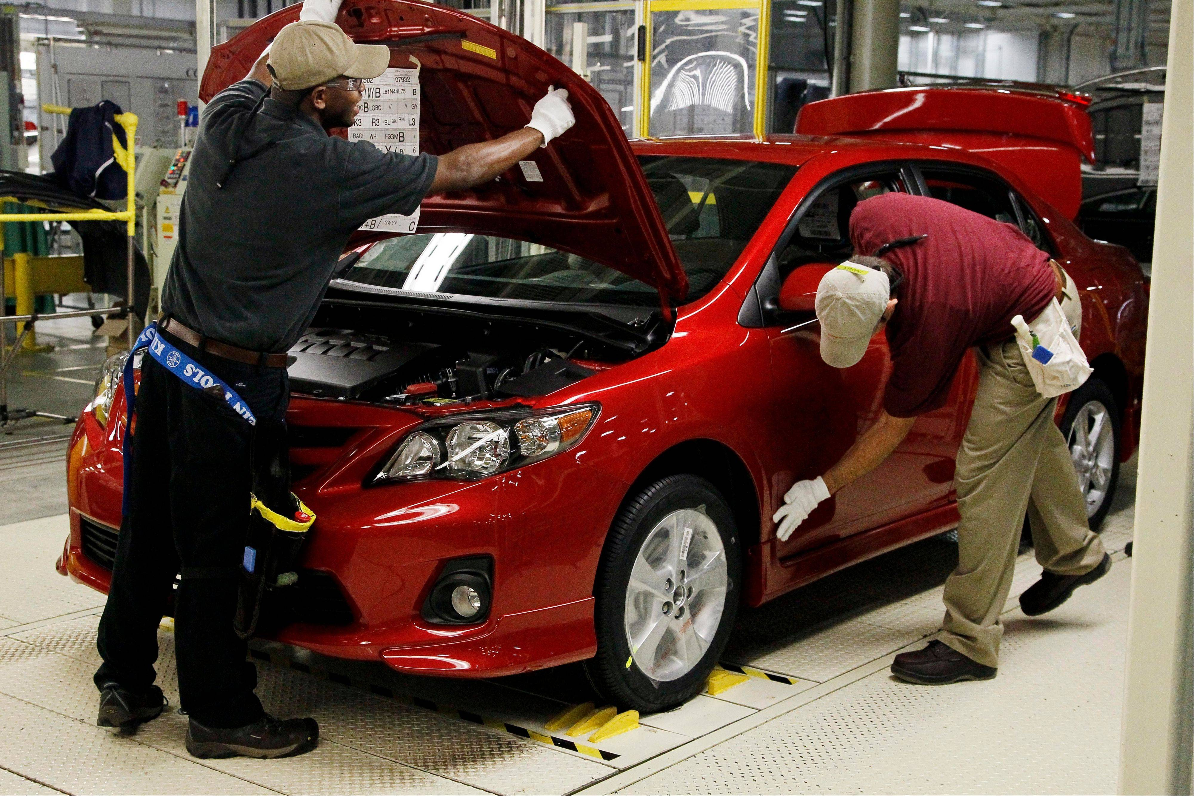 Toyota team members work on the final inspection of the Corolla automobile assembly line in Blue Springs, Miss. Toyota and other Japanese auto makers dominated the annual Consumer Reports reliability rankings.
