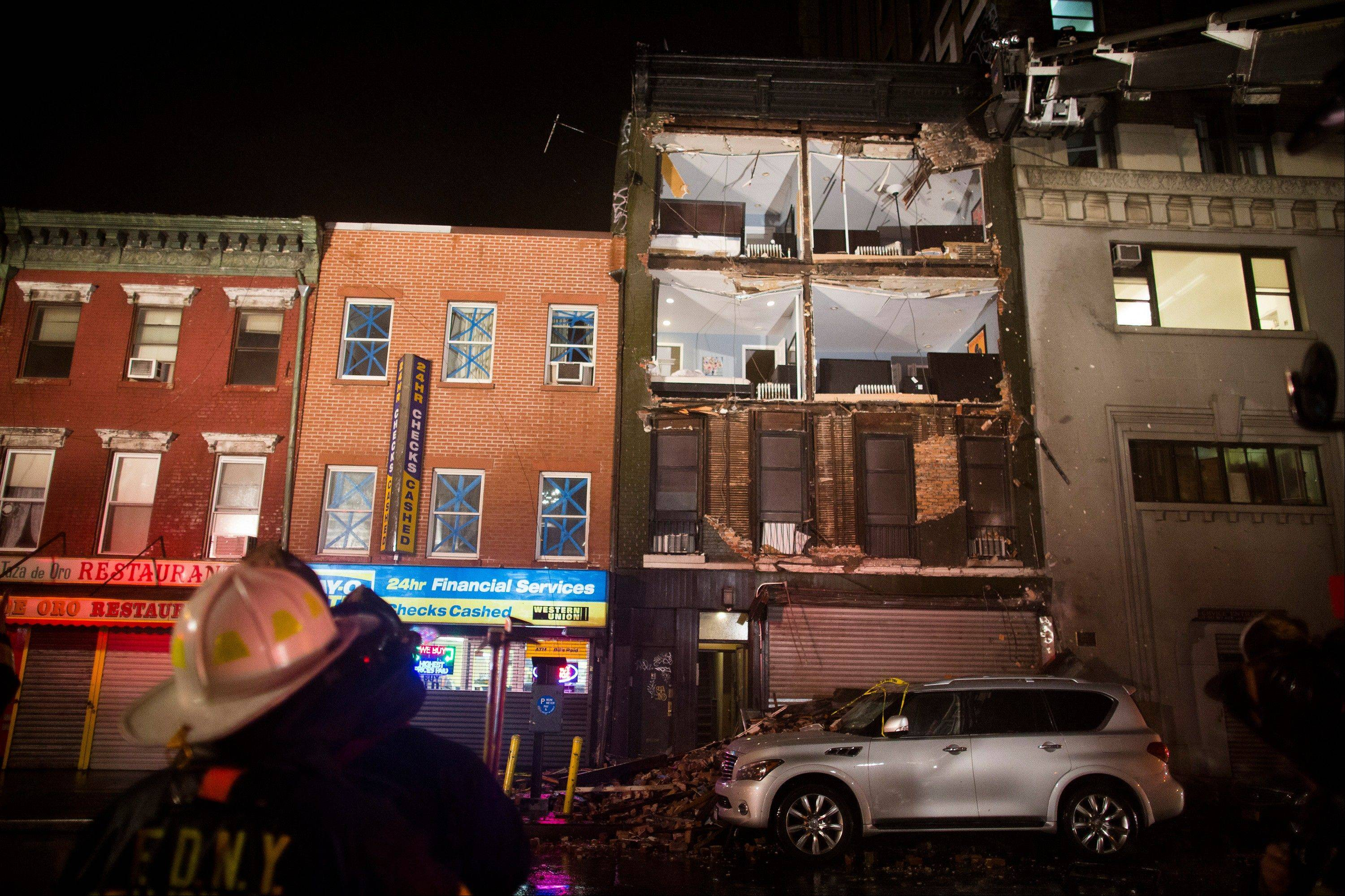 Firefighters look up at the facade of a four-story building on 14th Street and 8th Avenue that collapsed onto the sidewalk Monday, Oct. 29, 2012, in New York. Hurricane Sandy bore down on the Eastern Seaboard's largest cities Monday, forcing the shutdown of mass transit, schools and financial markets, sending coastal residents fleeing, and threatening a dangerous mix of high winds, soaking rain and a surging wall of water up to 11 feet tall.