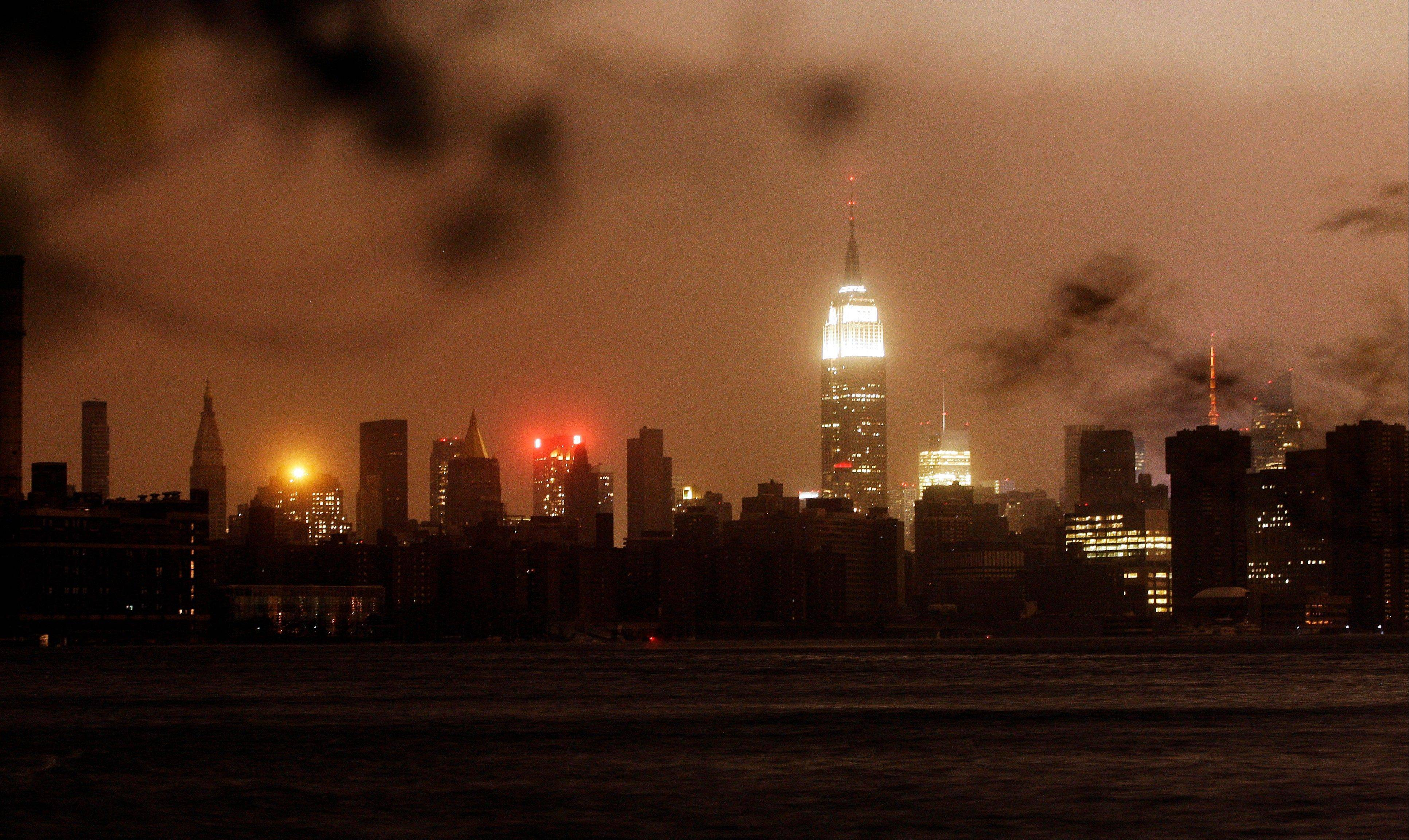 The New York skyline remains dark Monday, Oct. 29, 2012, as seen from the Williamsburg neighborhood in the Brooklyn borough of New York. In an attempt to lessen damage from saltwater to the subway system and the electrical network beneath the city's financial district, New York City's main utility cut power to about 6,500 customers in lower Manhattan. But a far wider swath of the city was hit with blackouts caused by flooding and transformer explosions.