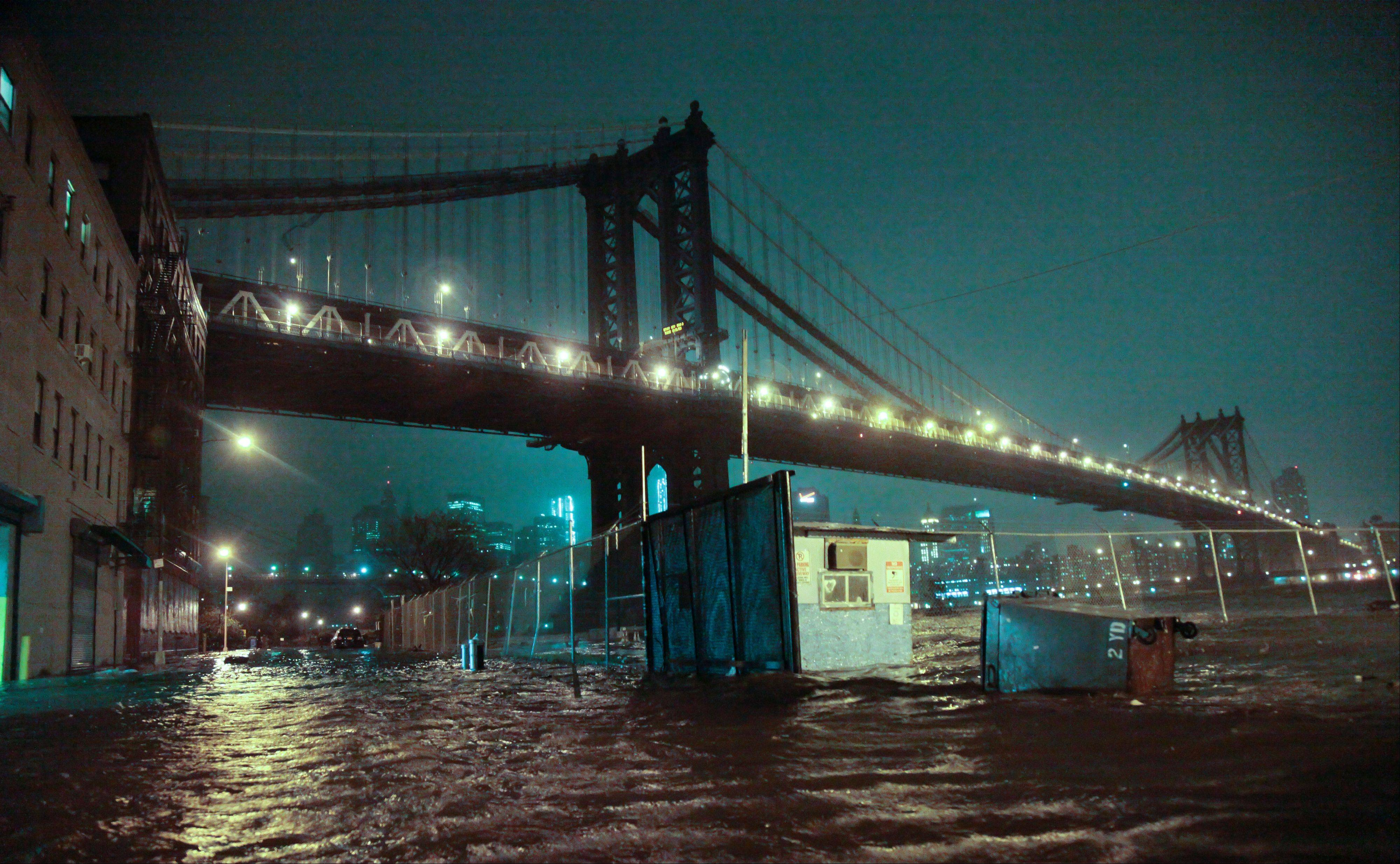 Streets are flooded under the Manhattan Bridge in the Dumbo section of Brooklyn, N.Y., Monday, Oct. 29, 2012. Sandy continued on its path Monday, as the storm forced the shutdown of mass transit, schools and financial markets, sending coastal residents fleeing, and threatening a dangerous mix of high winds and soaking rain.