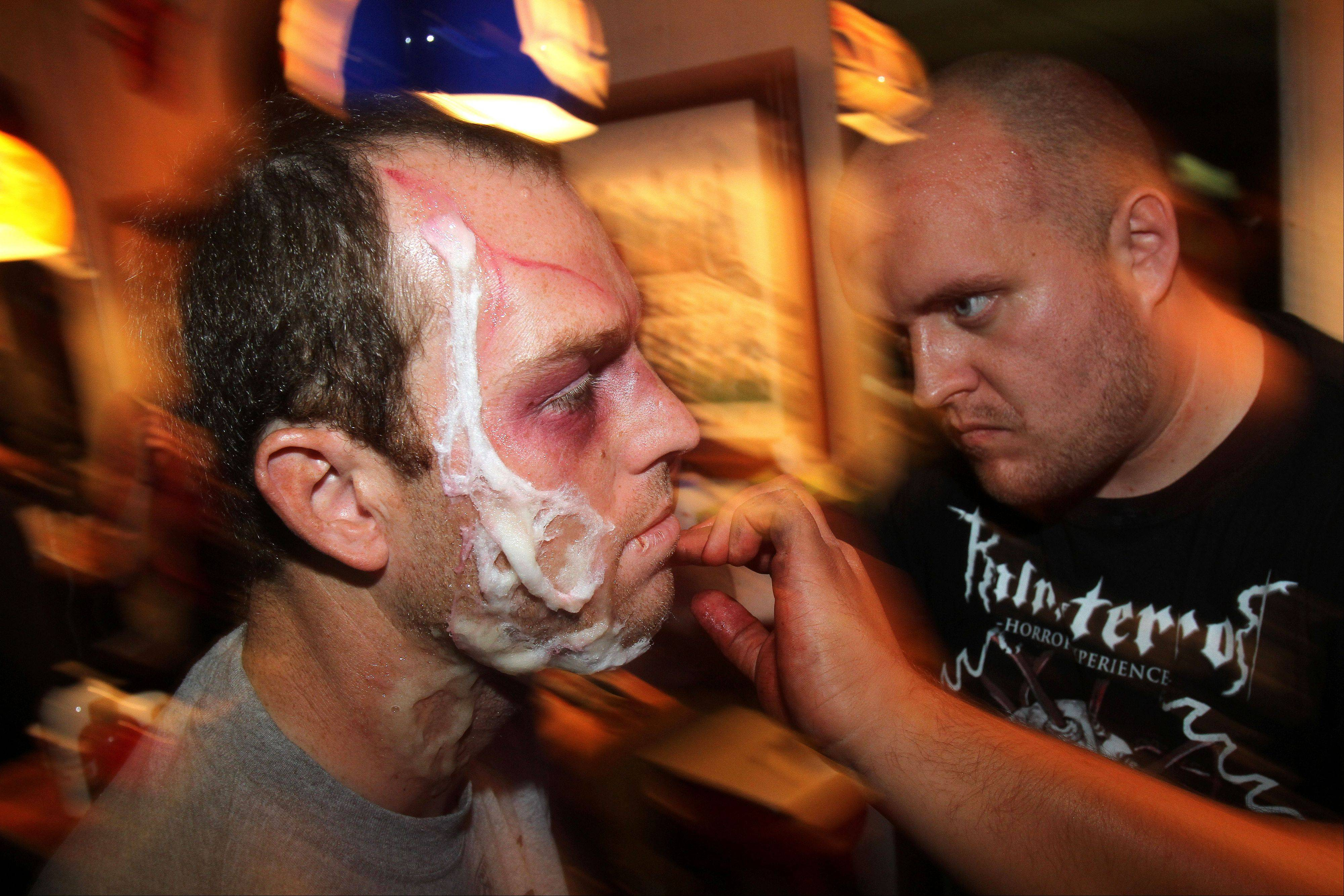 Makeup artist Ken Svitak of Round Lake turns Bears kicker Robbie Gould into a monster on Monday at the Realm of Terror haunted house at Kristof's Family Fun Center in Round Lake Beach.