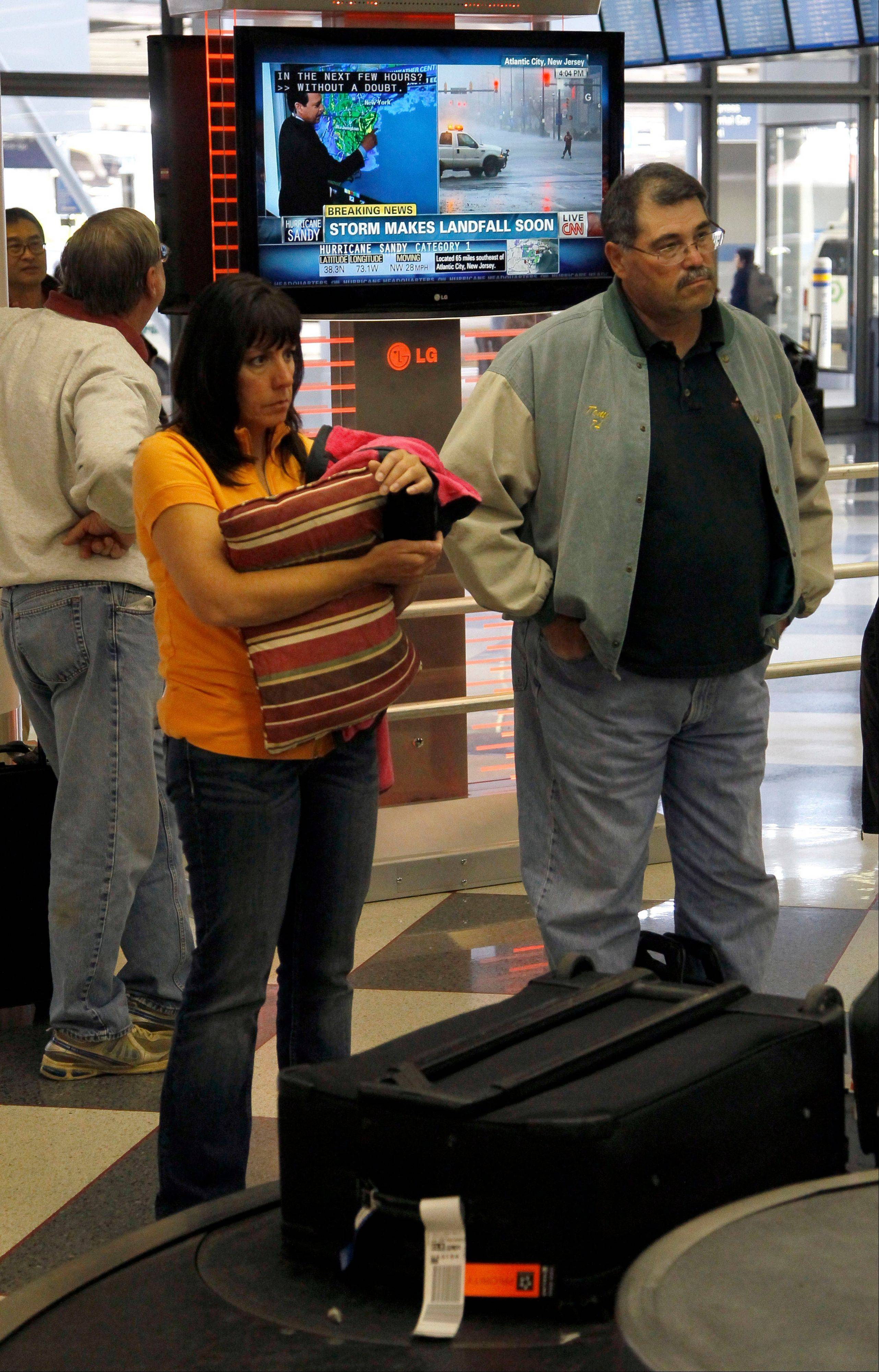 Travelers wait for their luggage at Chicago's O'Hare International Airport as a live update on Hurricane Sandy is broadcast, Monday.