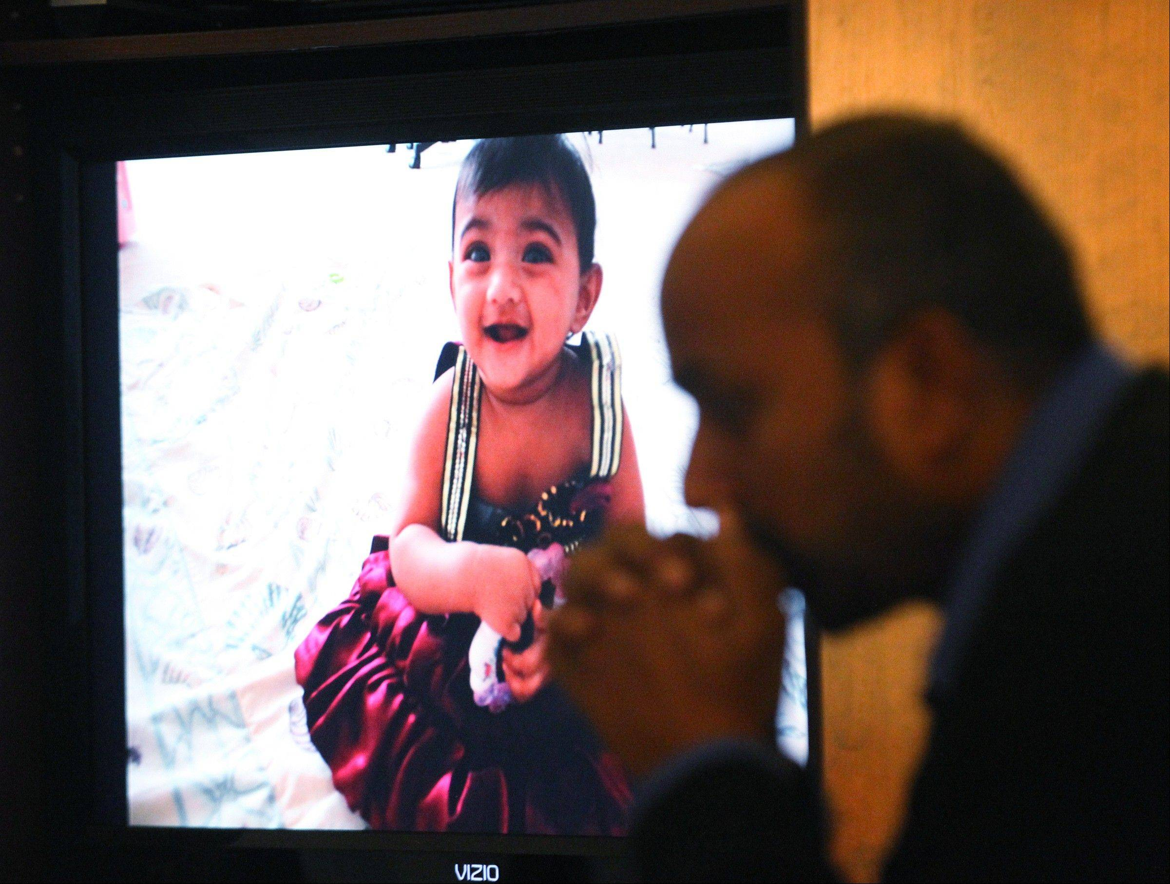 A slideshow of Saanvi Venna plays in the lobby of the Boyd-Horrox Funeral Home in Norristown, Pa., as Subash Karra sits nearby Sunday during a viewing for the 10-month-old girl, who was found dead after being kidnapped last week from her home in a Philadelphia suburb. Saanvi's grandmother was also killed.