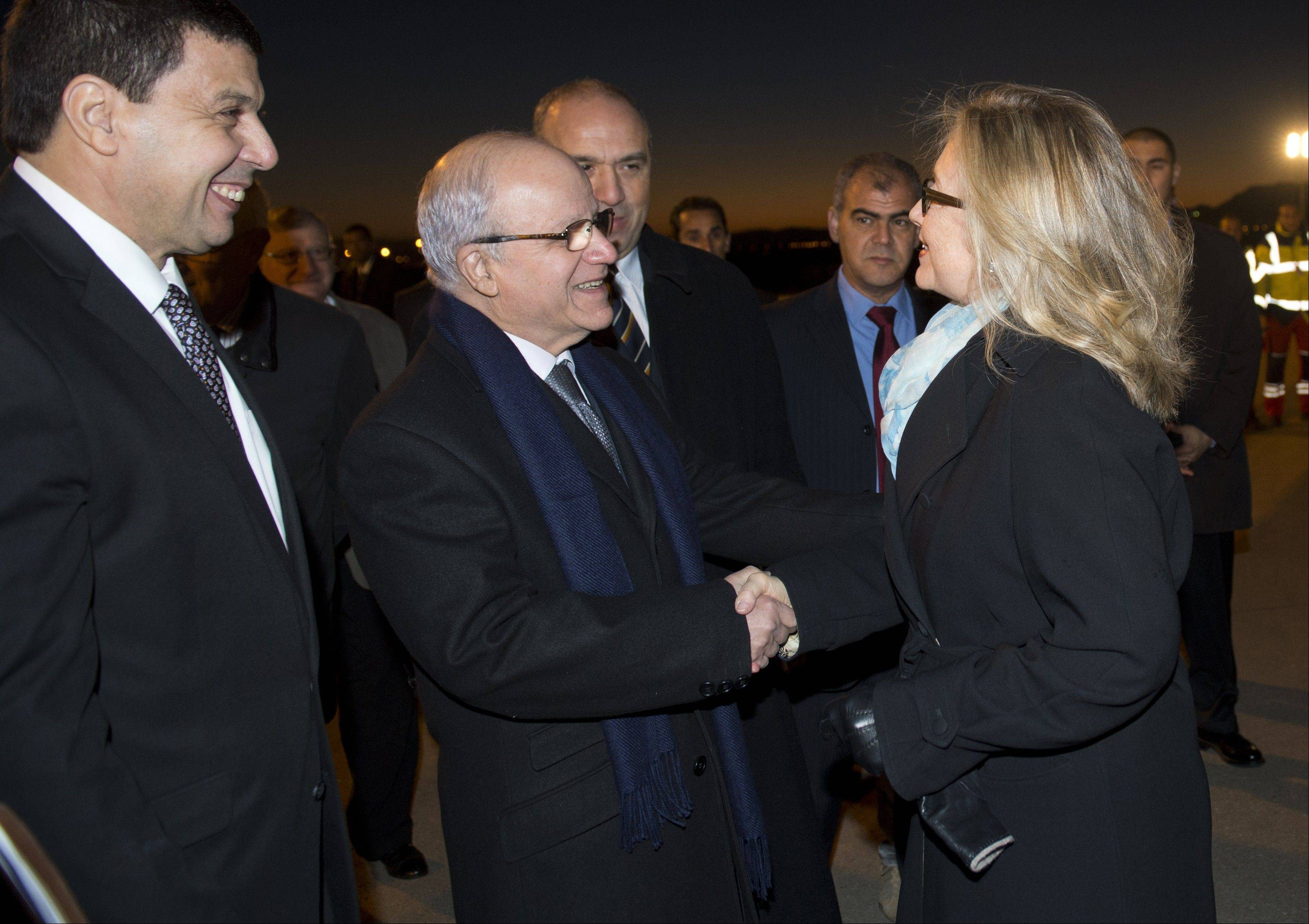 Algerian Foreign Minister Mourad Medelci, center, greets U.S. Secretary of State Hillary Rodham Clinton, upon her arrival at Houari Boumediene Airport, in Algiers, Algeria, Monday. Clinton is on a five-day trip overseas to increase pressure on Mali's al-Qaida-linked rebels and help Balkan nations end long-simmering ethnic and political disagreements.