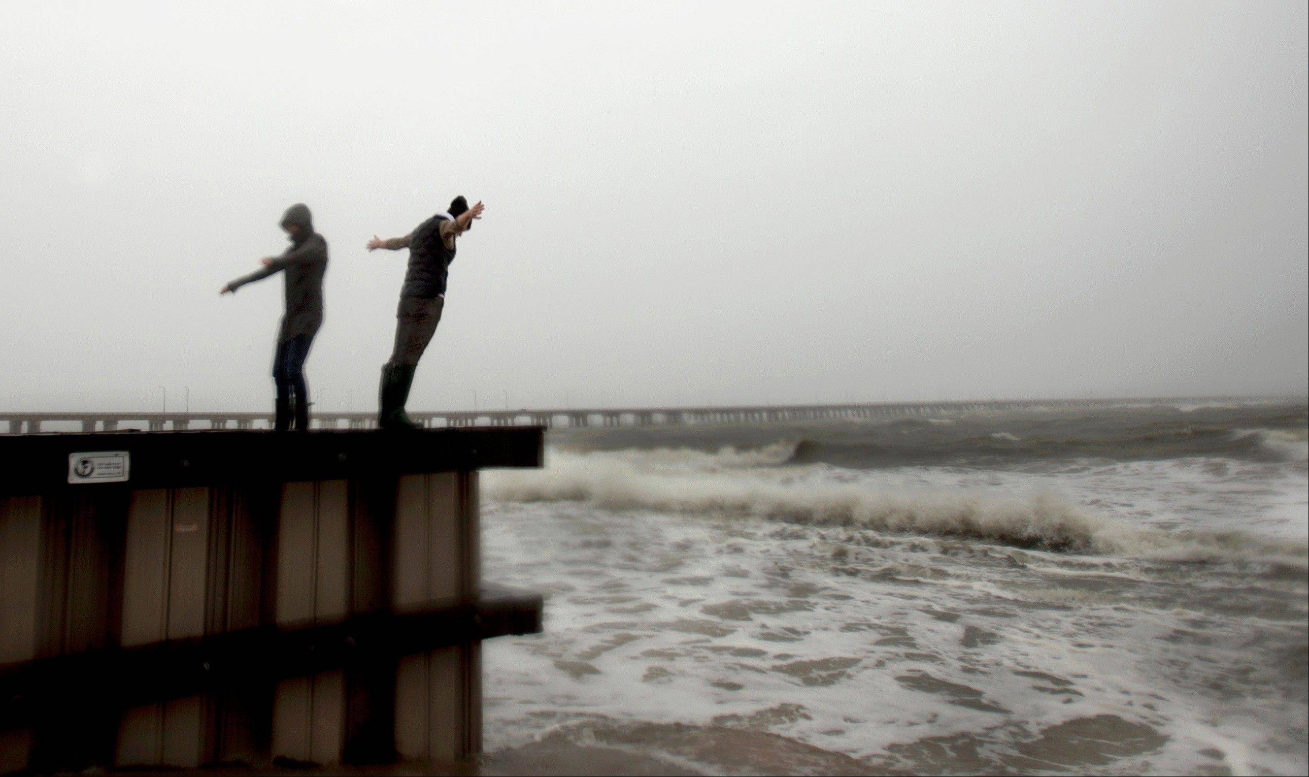 Jessica Ospina, left, and Allison Kane of Virginia Beach, Va., lean into the strong wind and rain off the Chesapeake Bay near the Chesapeake Bay Bridge tunnel in Virginia Beach, as Hurricane Sandy works its way north, battering the U.S. East Coast.