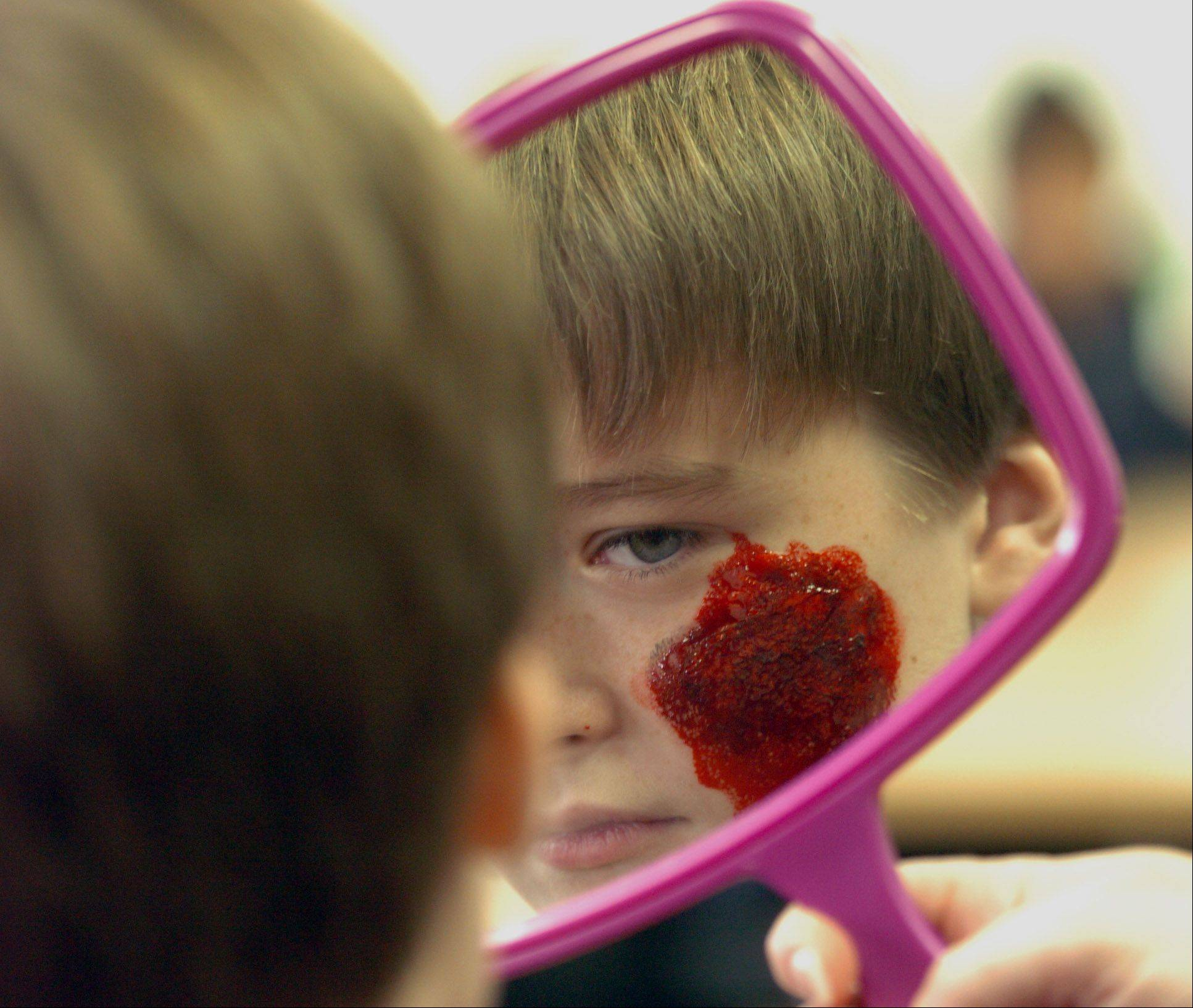 "Alex Schultz, 12, of Villa Park takes a look at his bloody face. He said,"" I like looking hurt!"" Children ages 12 to 19 get zombified by professional makeup artist Daniel Dudych at Helen Plum Library in Lombard Friday. Nearly a dozen children took part in this event."
