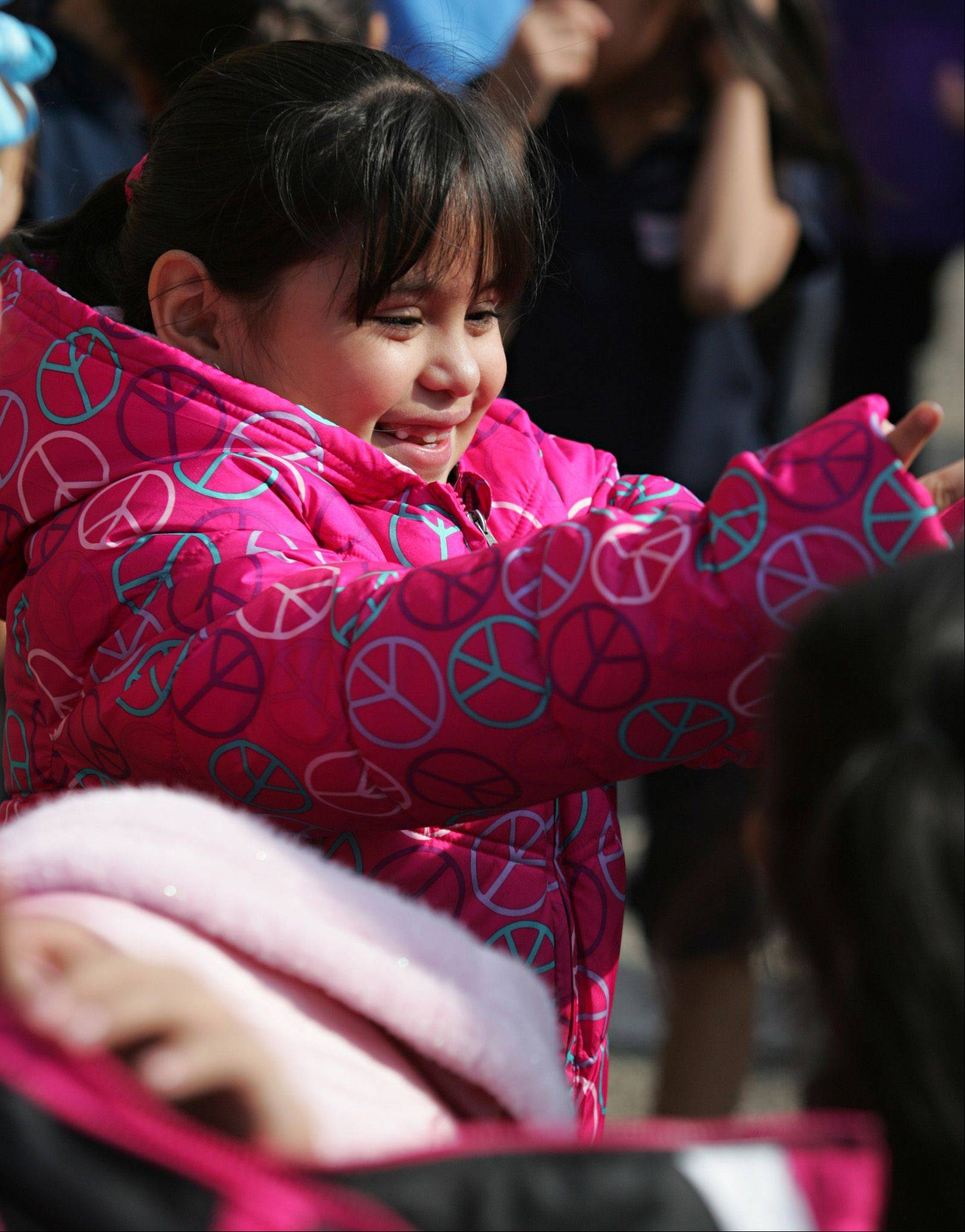 Second-grader Jasmin Casa�as grins as she tries on her new winter coat Wednesday at Sheridan Elementary in Elgin.