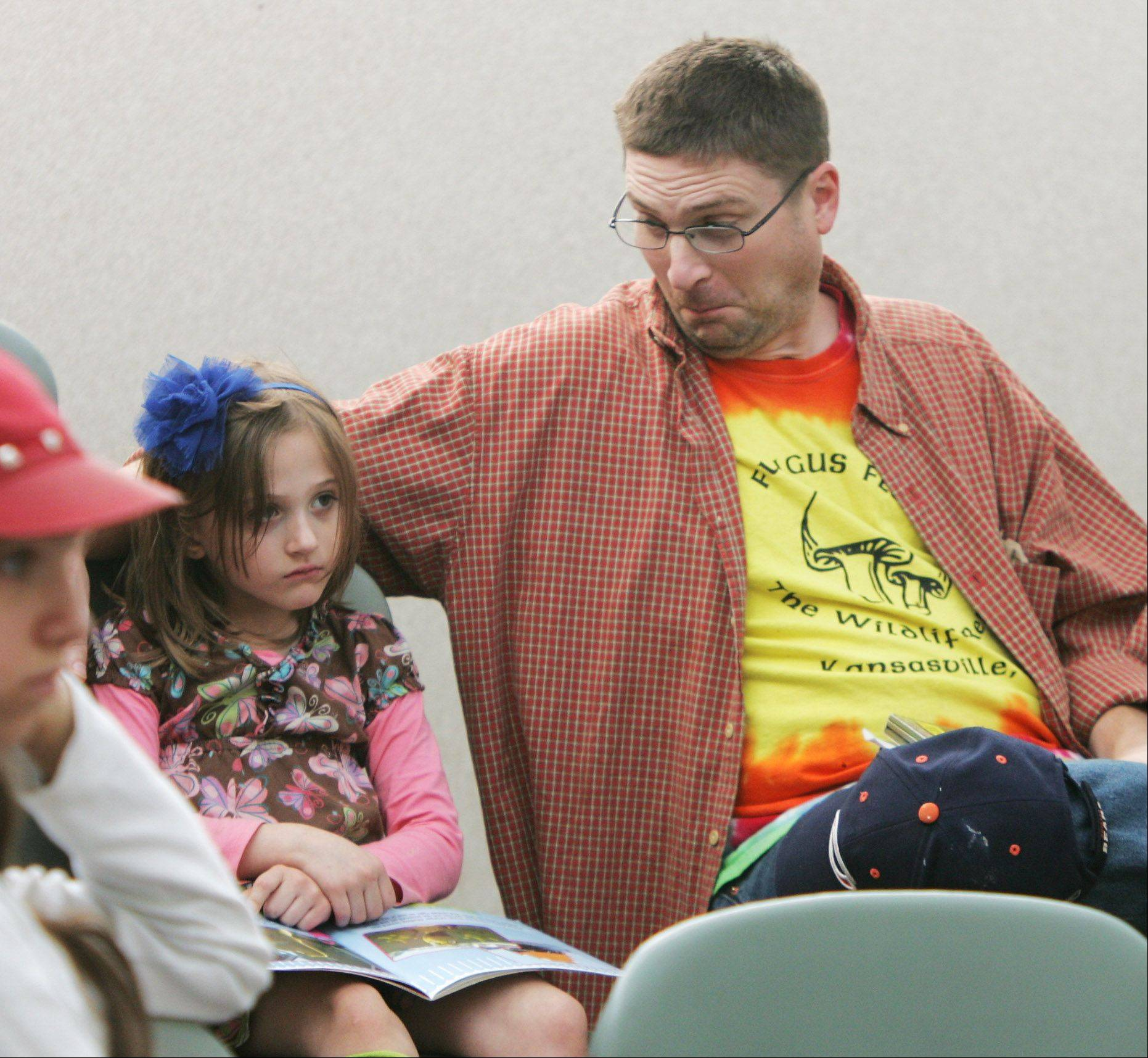 "Larry Littrell, of Lake Villa, reacts to a scene as he watches with his daughter, Zoe, 5, during the program ""This Girl Laughs, This Girl Cries, This Girl Does Nothing"" by the Lakes Community High School theater department Sunday at the Lake Villa District Library. The play is a modern Australian folk tale."