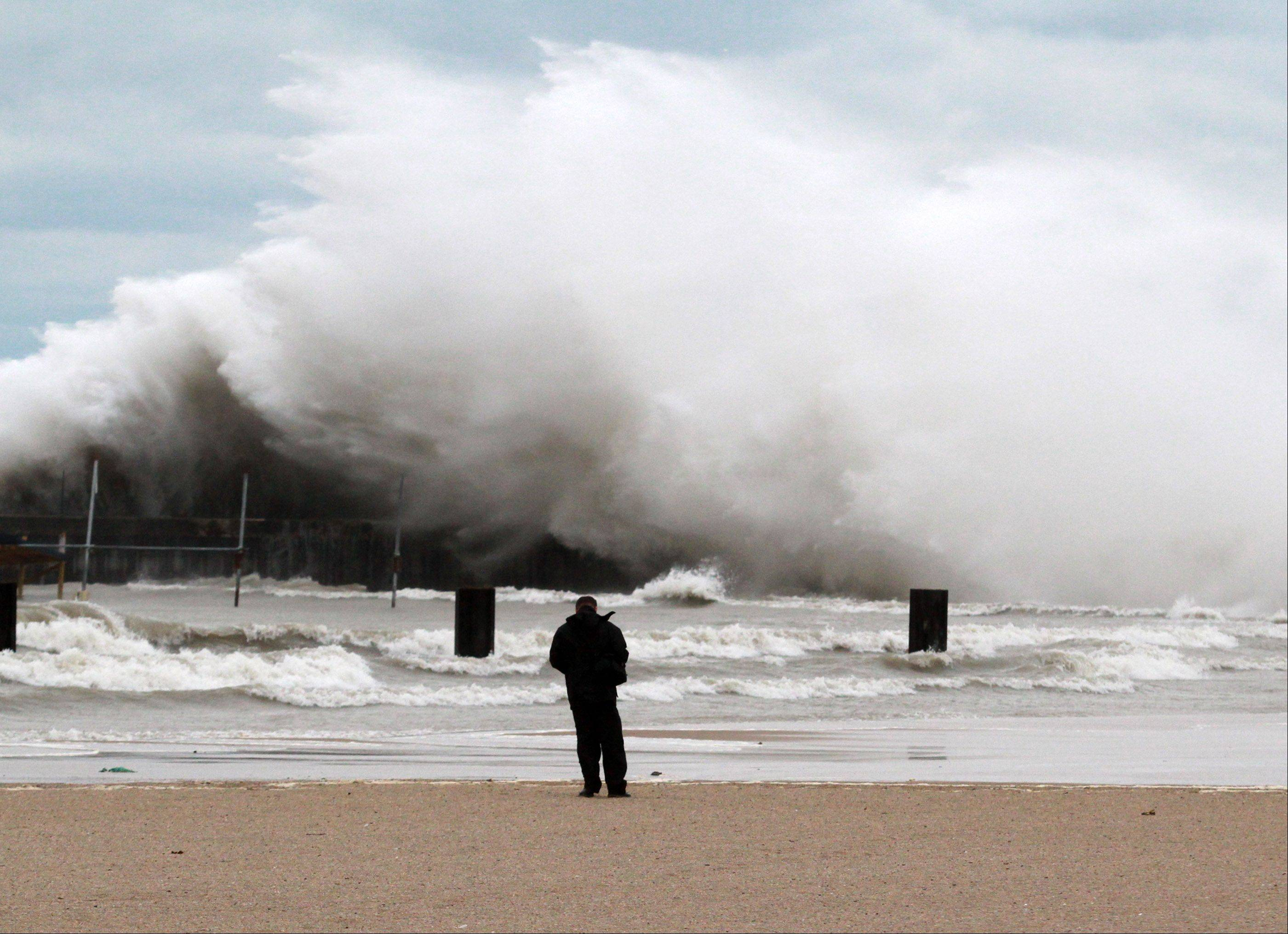 Alain Marginean of Chicago snaps photos of the massive waves that came ashore Tuesday morning on North Avenue Beach in Chicago. Waves as high as 20 feet pounded the city's lakefront Tuesday, an artifact of the superstorm that's devastated parts of the East Coast.