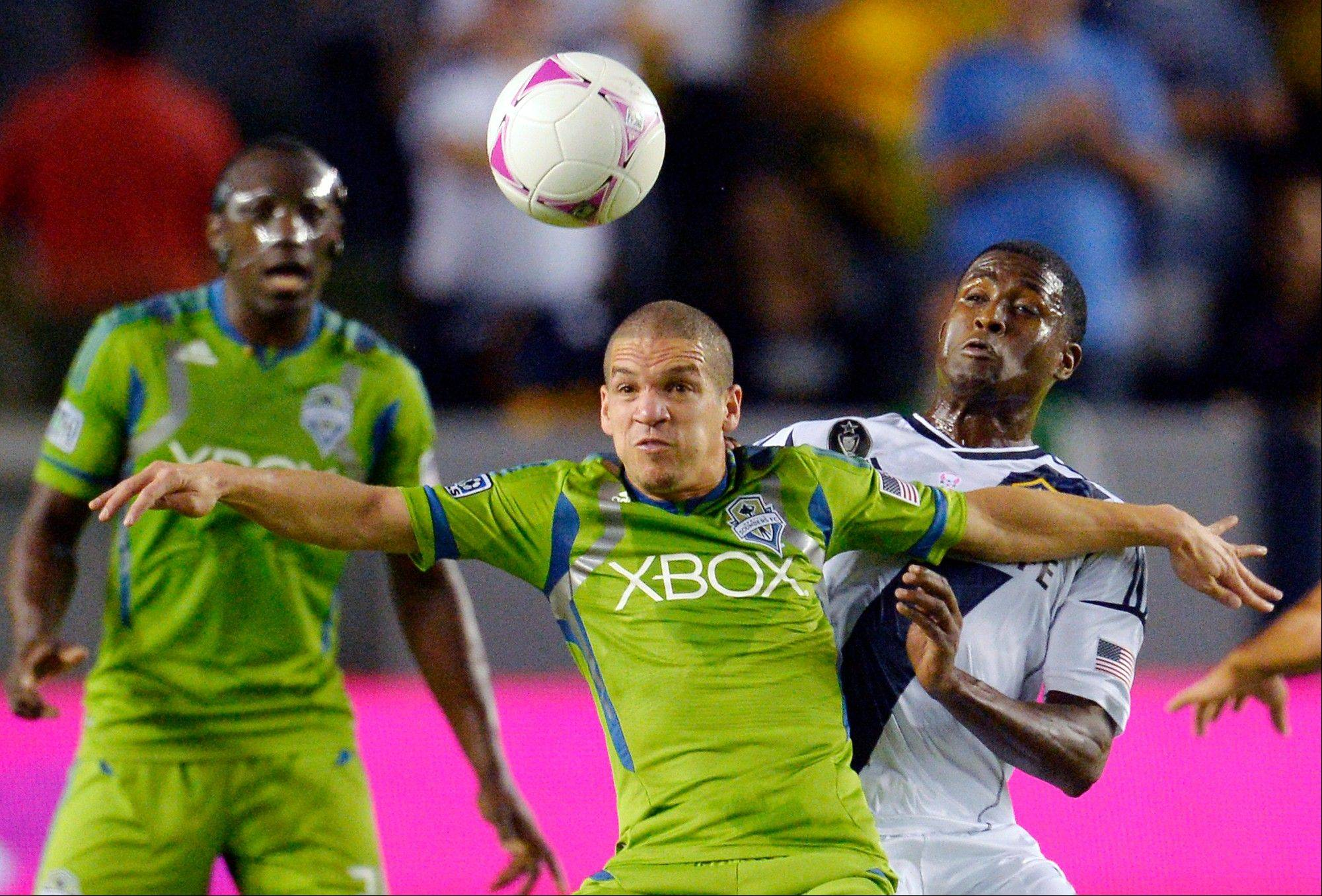 Seattle Sounders FC midfielder Osvaldo Alonso, center, and Los Angeles Galaxy forward Edson Buddle battle for the ball as midfielder Brad Evans watches during the first half of their MLS soccer match, Sunday, Oct. 28, 2012, in Carson, Calif.