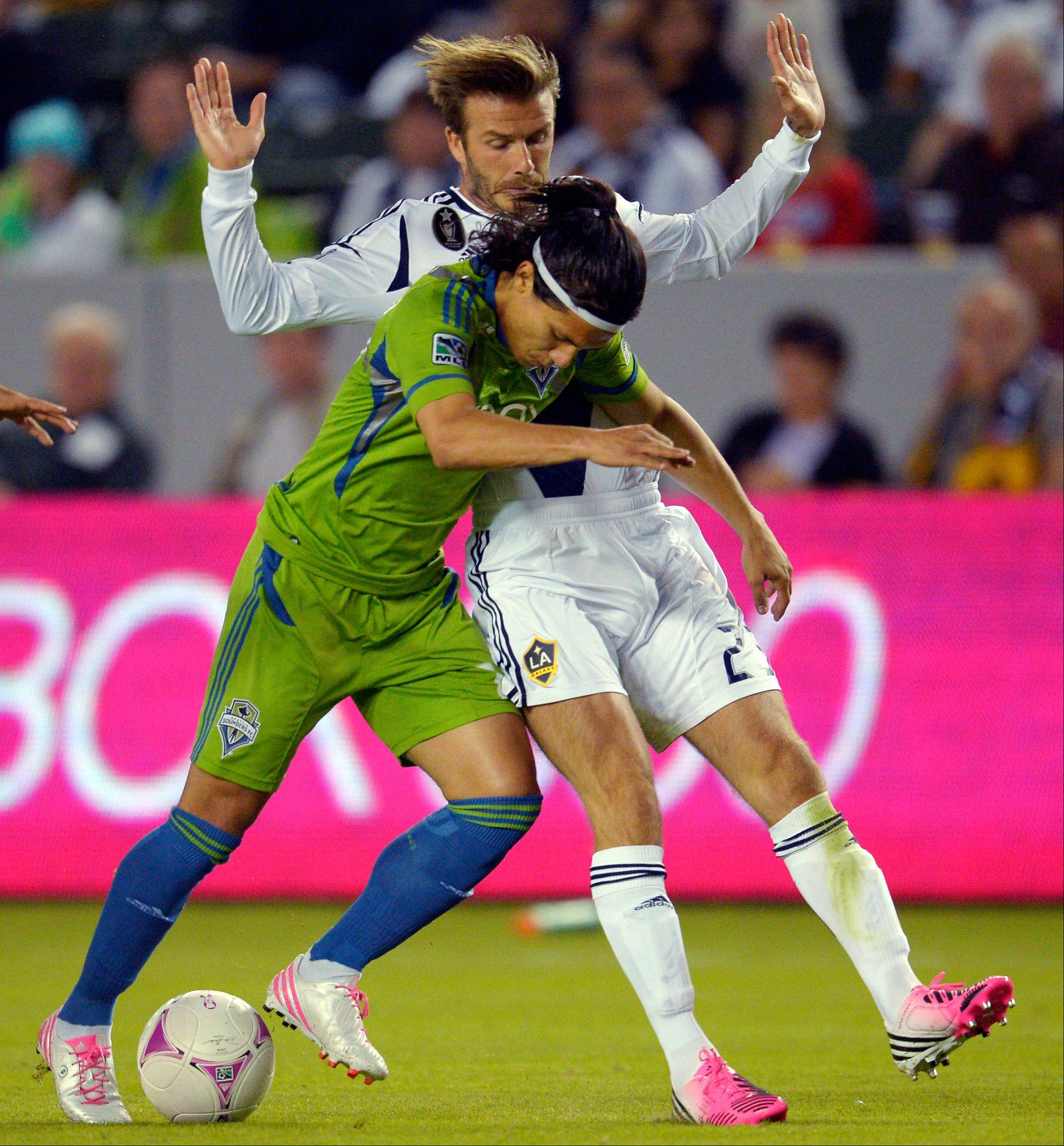 Seattle Sounders FC forward Fredy Montero, left, and Los Angeles Galaxy midfielder David Beckham battle for the ball during the first half of their MLS soccer match, Sunday, Oct. 28, 2012, in Carson, Calif. The Galaxy won 1-0.