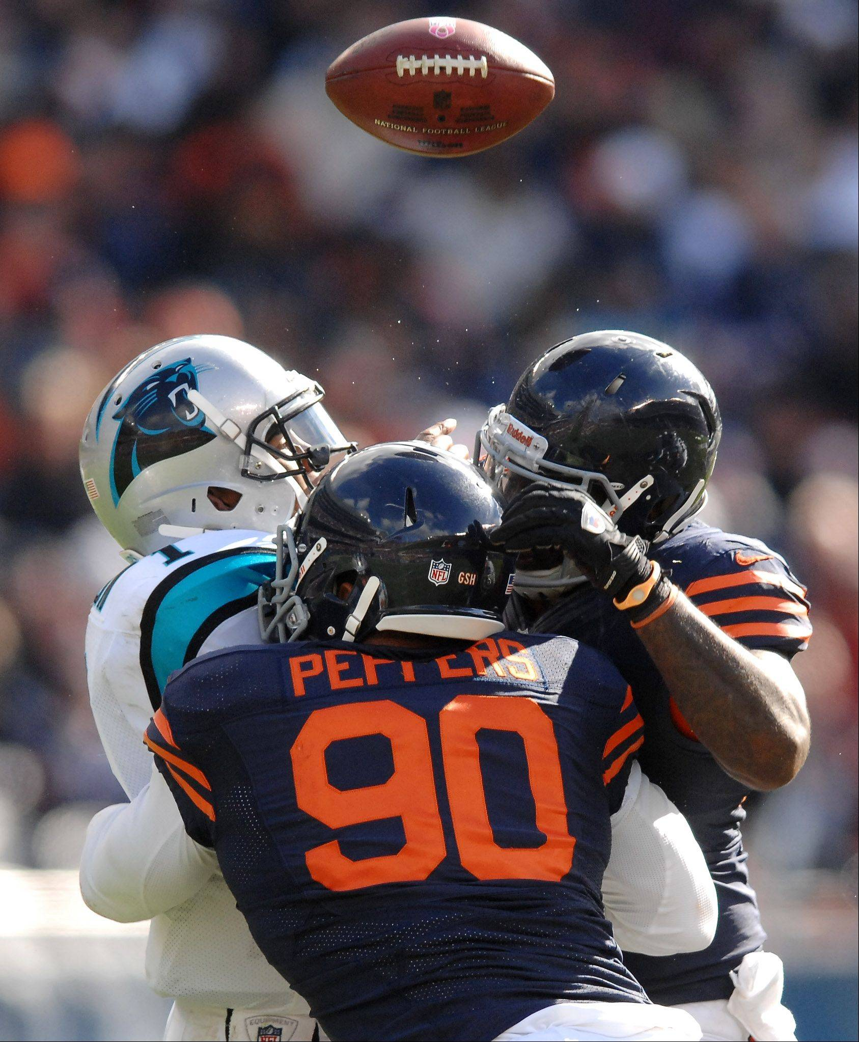 Carolina Panthers quarterback Cam Newton (1) fumbles into the air as he is sacked by Chicago's Julius Peppers and Henry Melton during Sunday's game at Soldier Field in Chicago. The Panthers recovered.