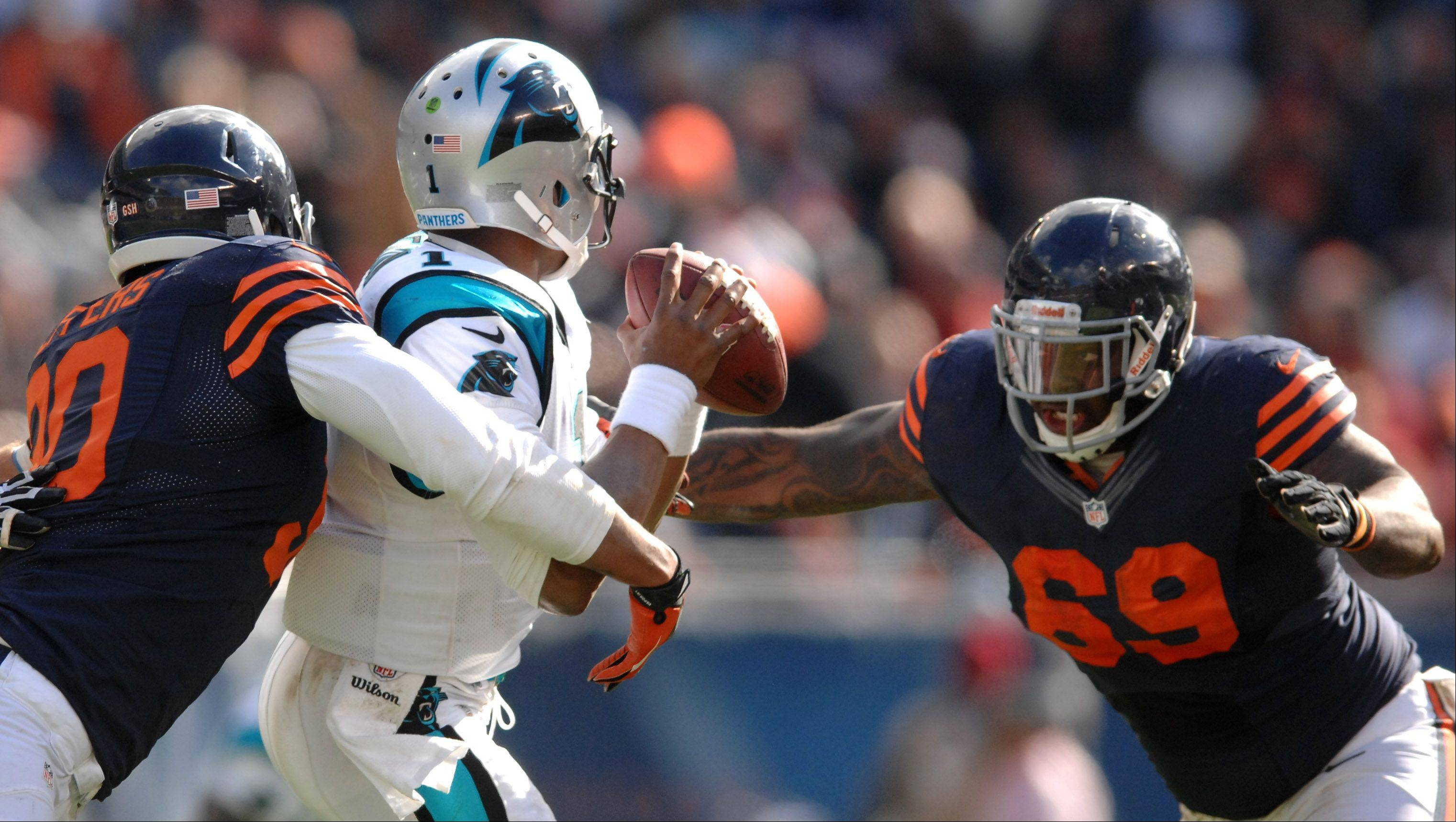 Chicago Bears defensive end Julius Peppers (90) and defensive tackle Henry Melton (69) converger for a sack of Carolina Panthers quarterback Cam Newton (1) during Sunday's game at Soldier Field in Chicago.