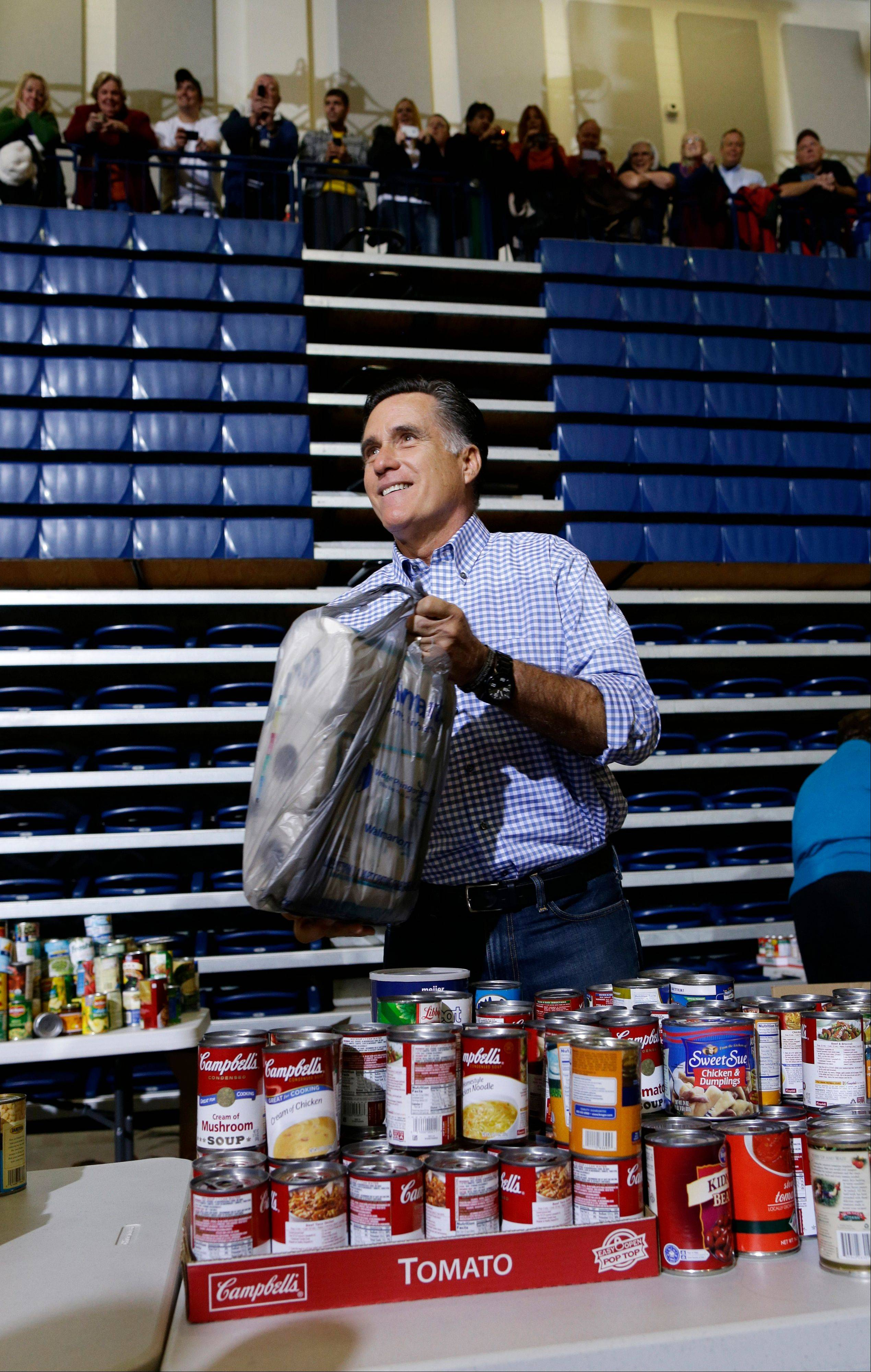 Republican presidential candidate, former Massachusetts Gov. Mitt Romney holds a bag of paper towels as he participates in a campaign event collecting supplies from residents and local relief organizations for victims of superstorm Sandy on Tuesday in Kettering, Ohio.
