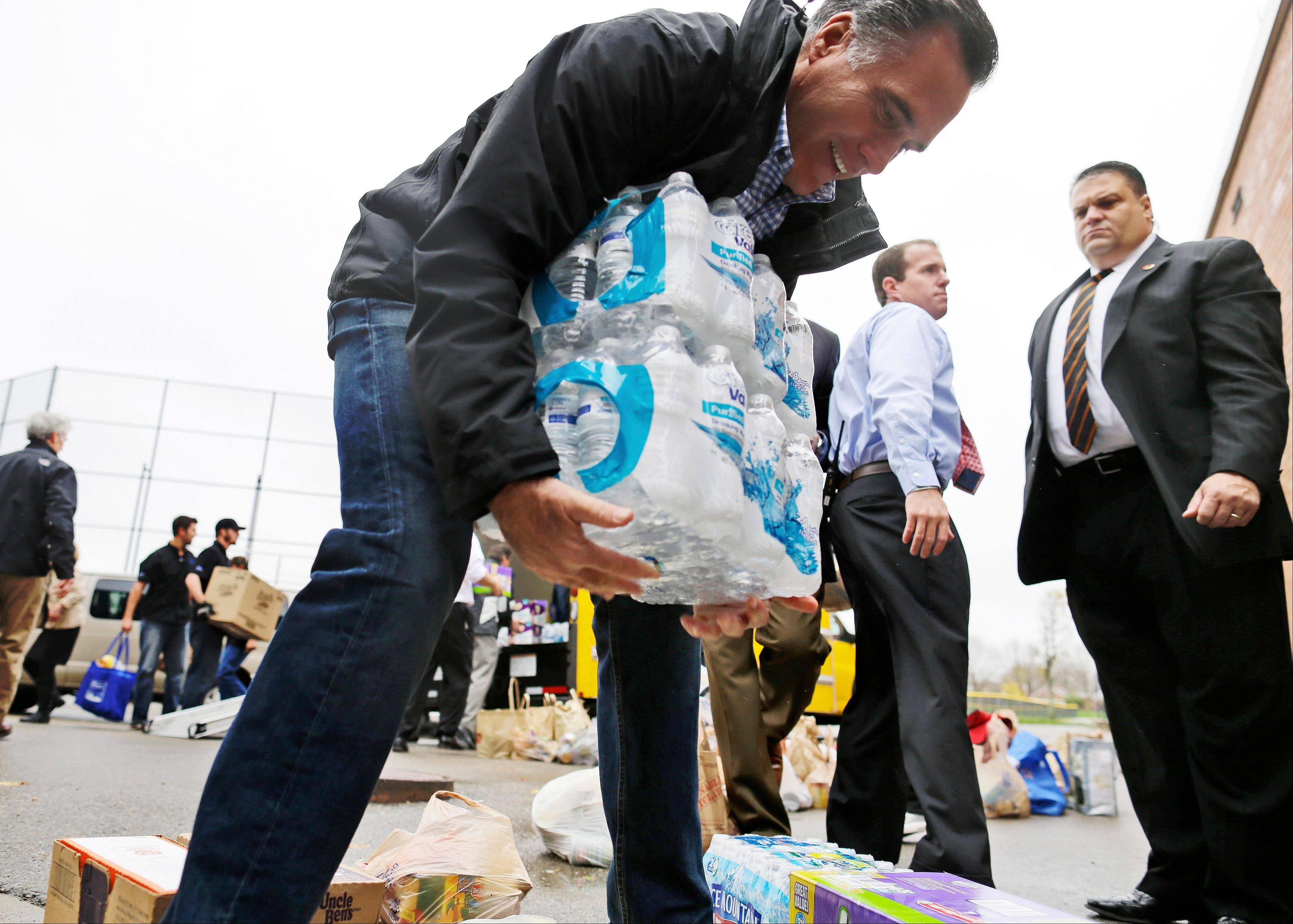 Republican presidential candidate, former Massachusetts Gov. Mitt Romney lifts bottles of water to load into a truck as he participates in a campaign event collecting supplies from residents and local relief organizations for victims of superstorm Sandy on Tuesday in Kettering, Ohio.