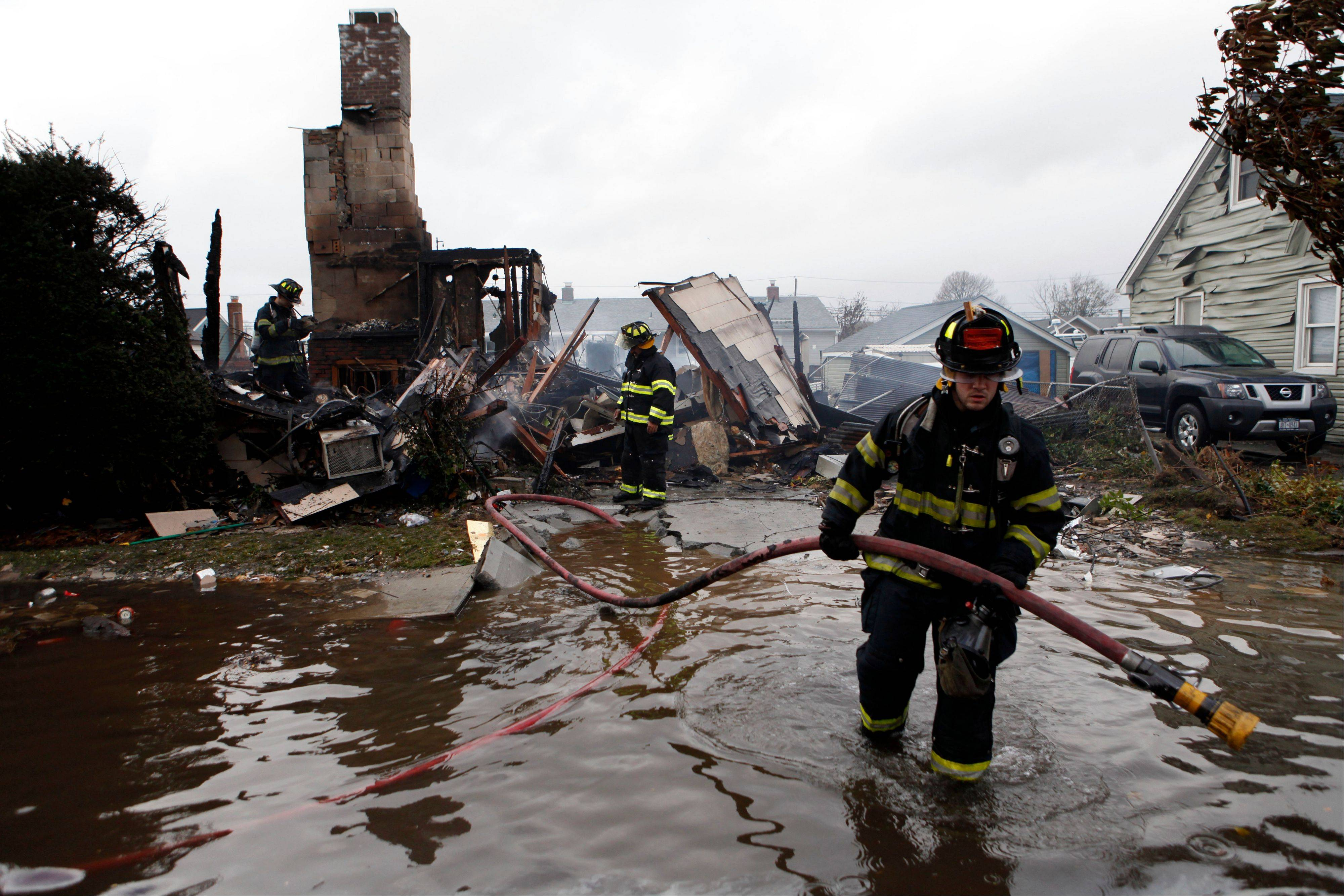 Firefighters work at the scene of a house fire in the aftermath of superstorm Sandy, Tuesday, Oct. 30, 2012, in Lindenhurst, N.Y. According to firefighters at the scene, four homes were destroyed by fire overnight in Lindenhurst, and six in Massapequa.