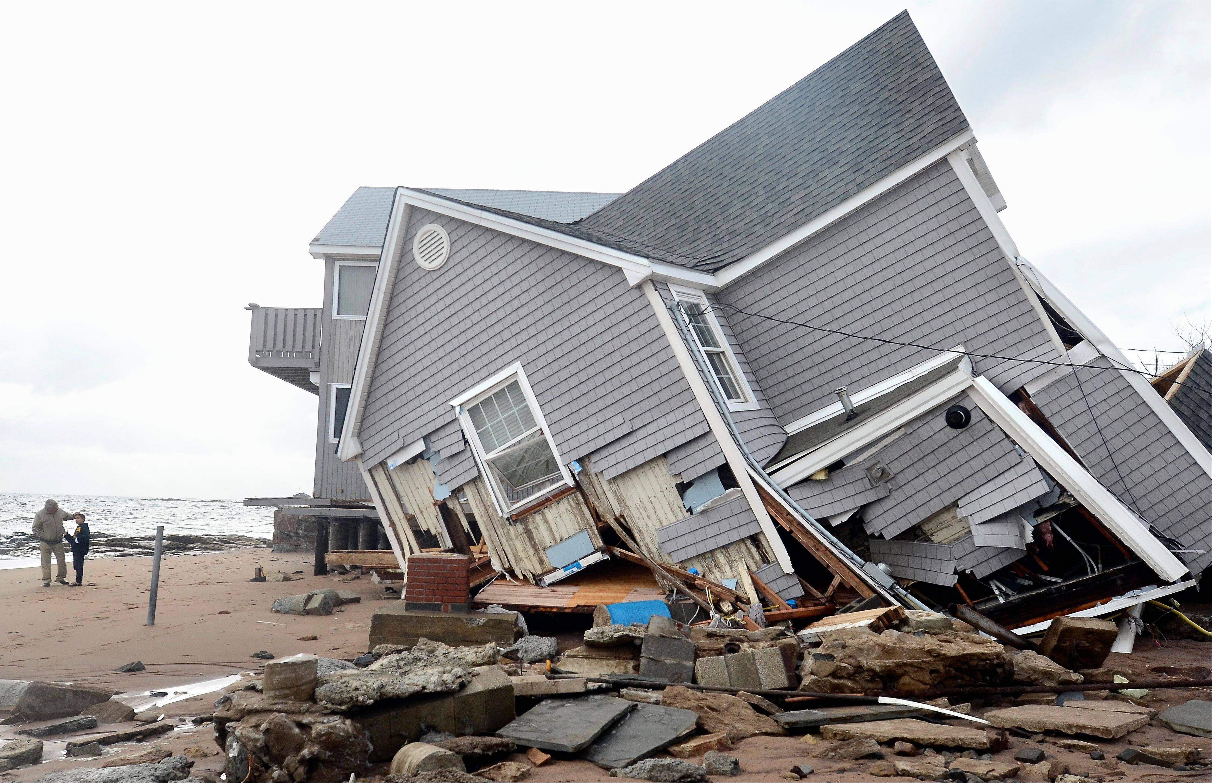 People stand next to a house collapsed from superstorm Sandy in East Haven, Conn., Tuesday.