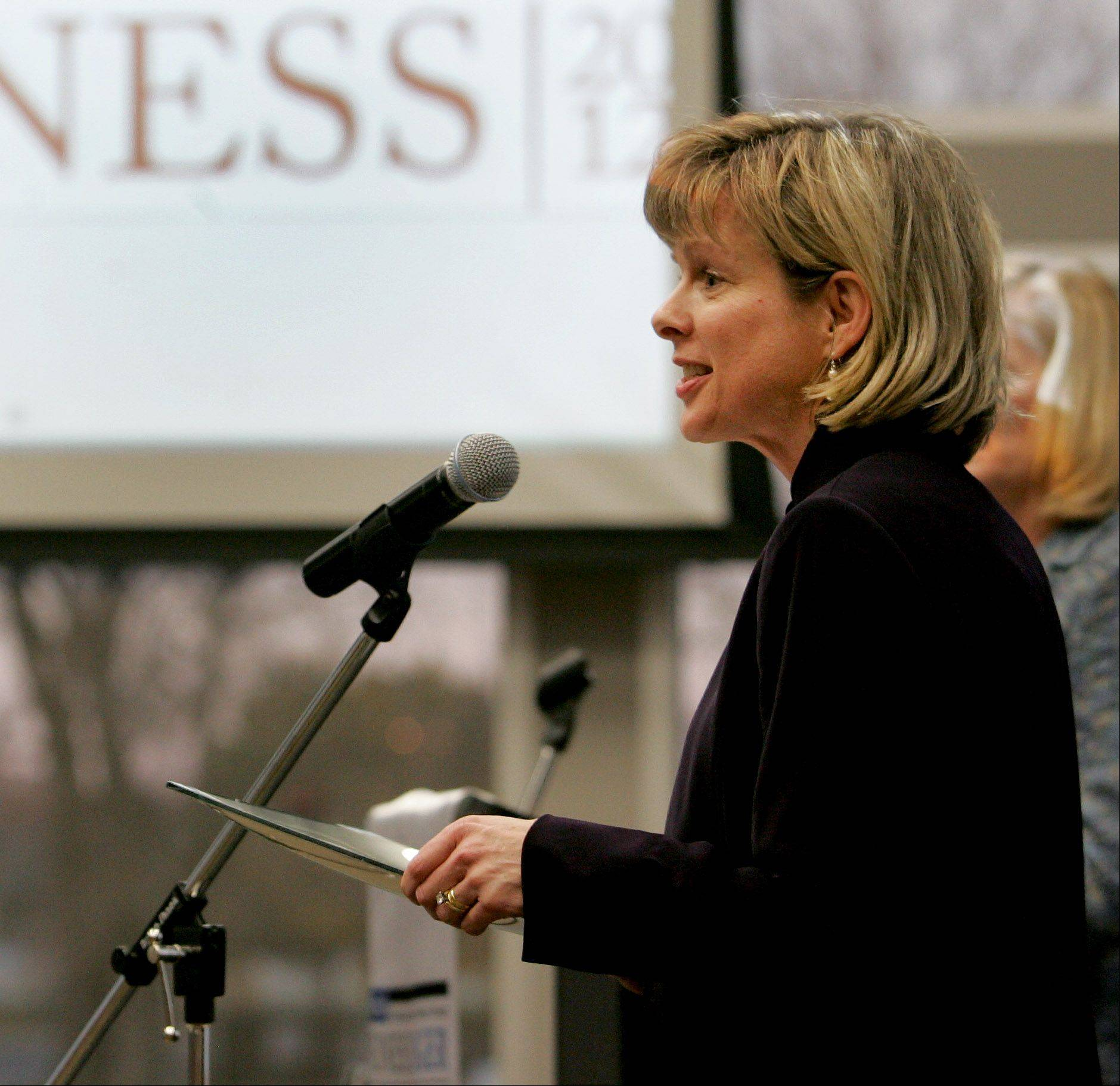 Bev Horne/bhorne@dailyherald.comKimberly Coogan, founder and partner, Bellock & Coogan Ltd., accepts her Influential Women in Business award at Northern Illinois University Naperville campus on Monday.