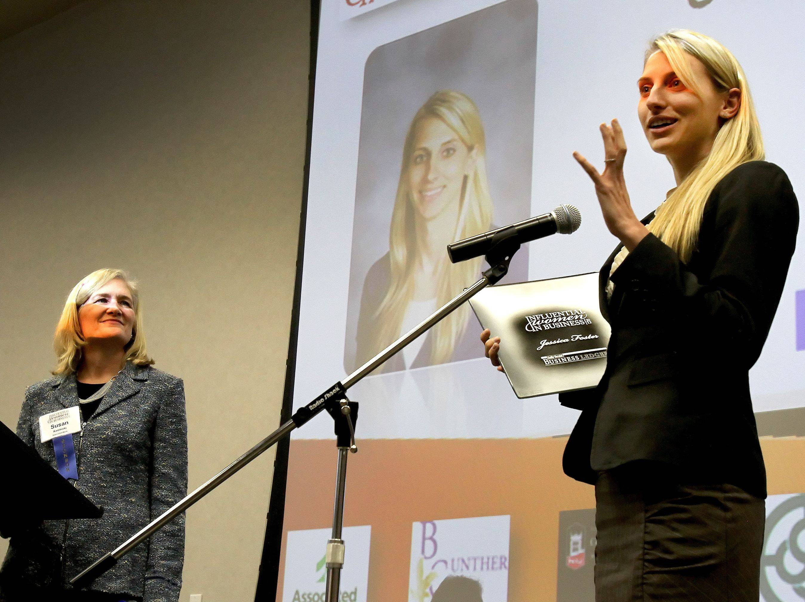 Jessica Foster, right, teacher at Lake Park High School, accepts her Influential Women in Business award at Northern Illinois University Naperville campus on Monday as Susan Kaminski of Associated Bank looks on.