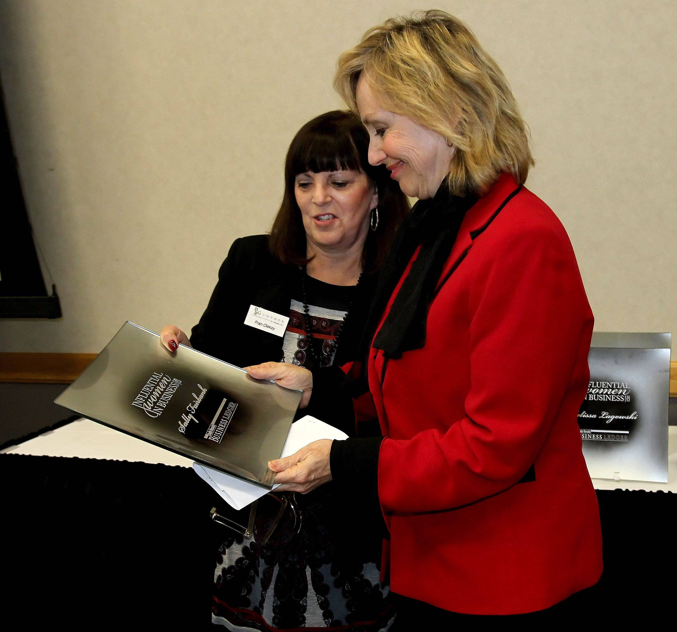 Fran Oleksy, with B. Gunther & Company, left, presents Sally Fairbank, director of Paralegal Studies Program at the College of DuPage, with the Influential Women in Business award at Northern Illinois University Naperville campus Monday.