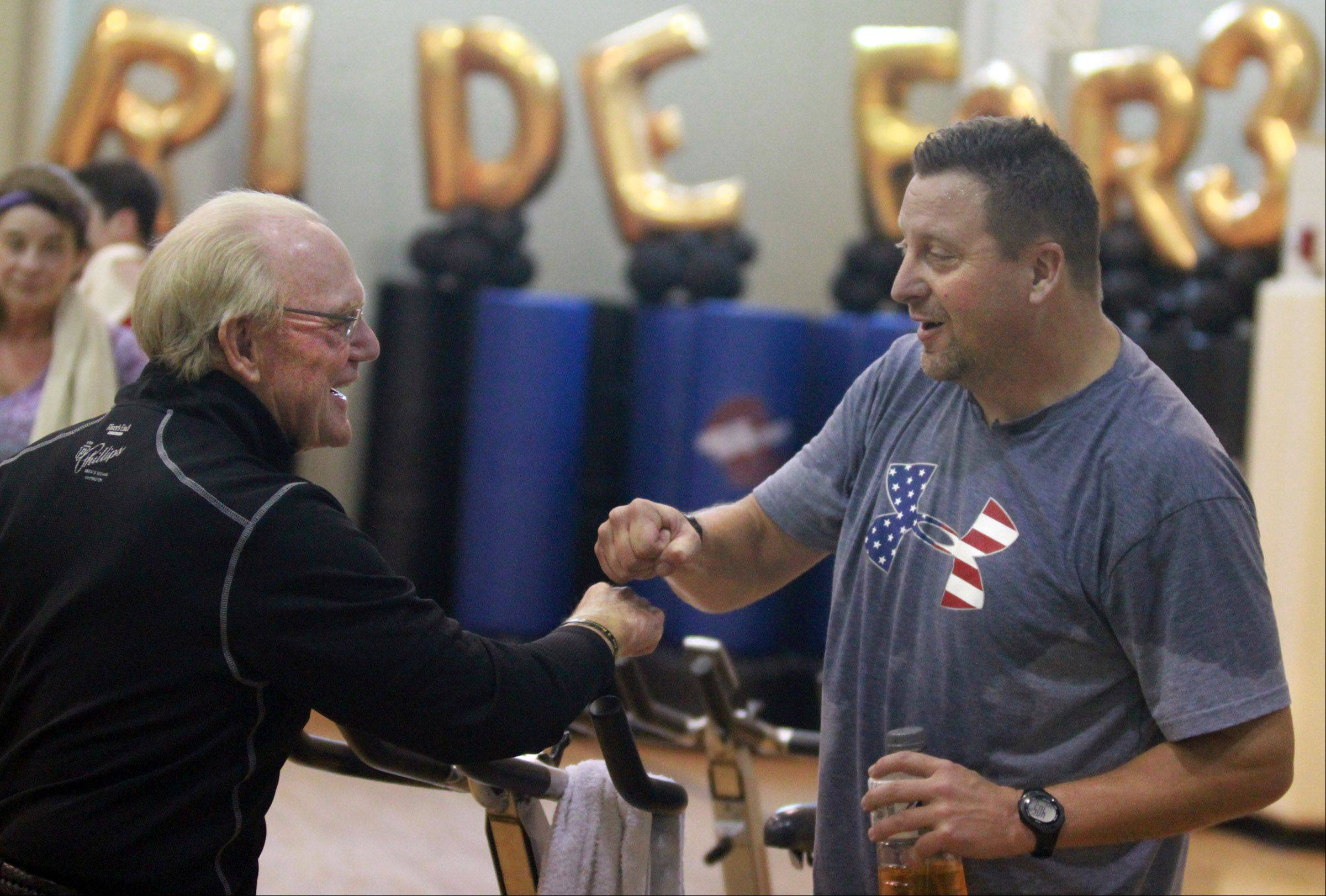 Bicyclist Bob Lee, 70, left, gets a fist bump from Thom Rosen, both of Barrington, after a one-hour stationary cycle fundraiser class, just before a welcome home reception for Lee at Good Shepherd Health and Fitness Center in Barrington Saturday.