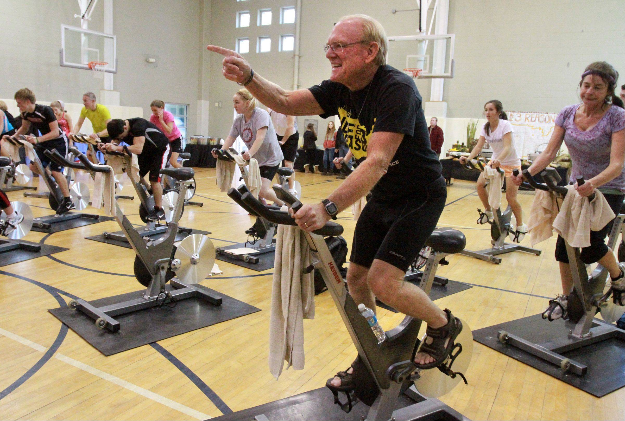 Bicyclist Bob Lee, 70, points to the instructor during a one-hour stationary cycle fundraiser class, just before a welcome home reception for Lee at Good Shepherd Health and Fitness Center in Barrington Saturday.