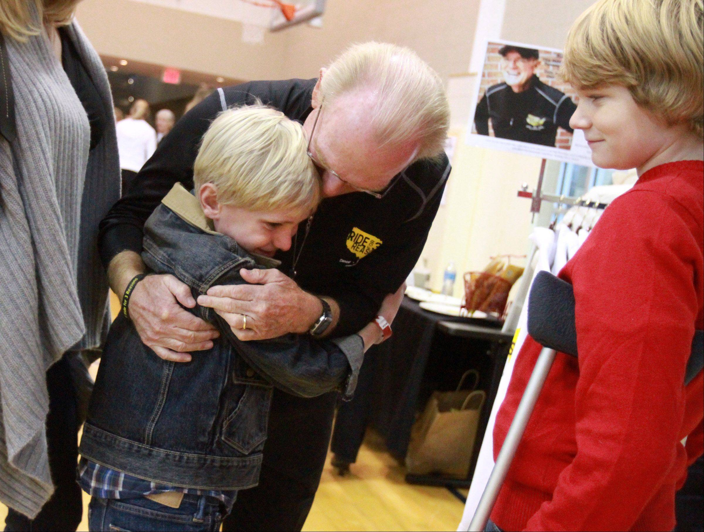 Barrington bicyclist Bob Lee, 70 gets a hug from family friend Parker Henry, 8, of Barrington, as Parker's brother Spencer, 13, looks on during a welcome home reception Saturday.
