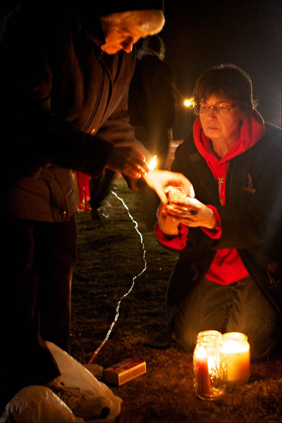 Leona Wieland, 65, of Sioux Falls, lights candles in peaceful protest with Sister Janice Klein, left, as they await the Tuesday execution in Sioux Falls, S.D., of South Dakota State Penitentiary inmate Donald Moeller.