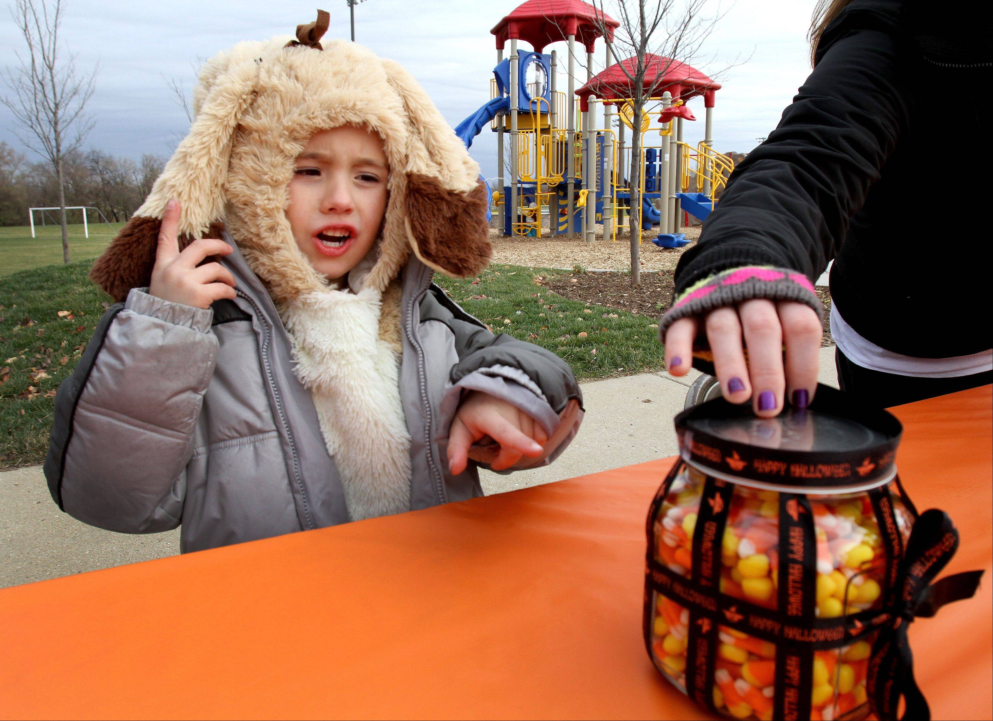 Jaden Holtz, 5, of Hanover Park, takes a guess on how many candy corns are in the jar, one of the activities offered Tuesday during the grand opening of the new playground outside the Clauss Recreation Center in Roselle.