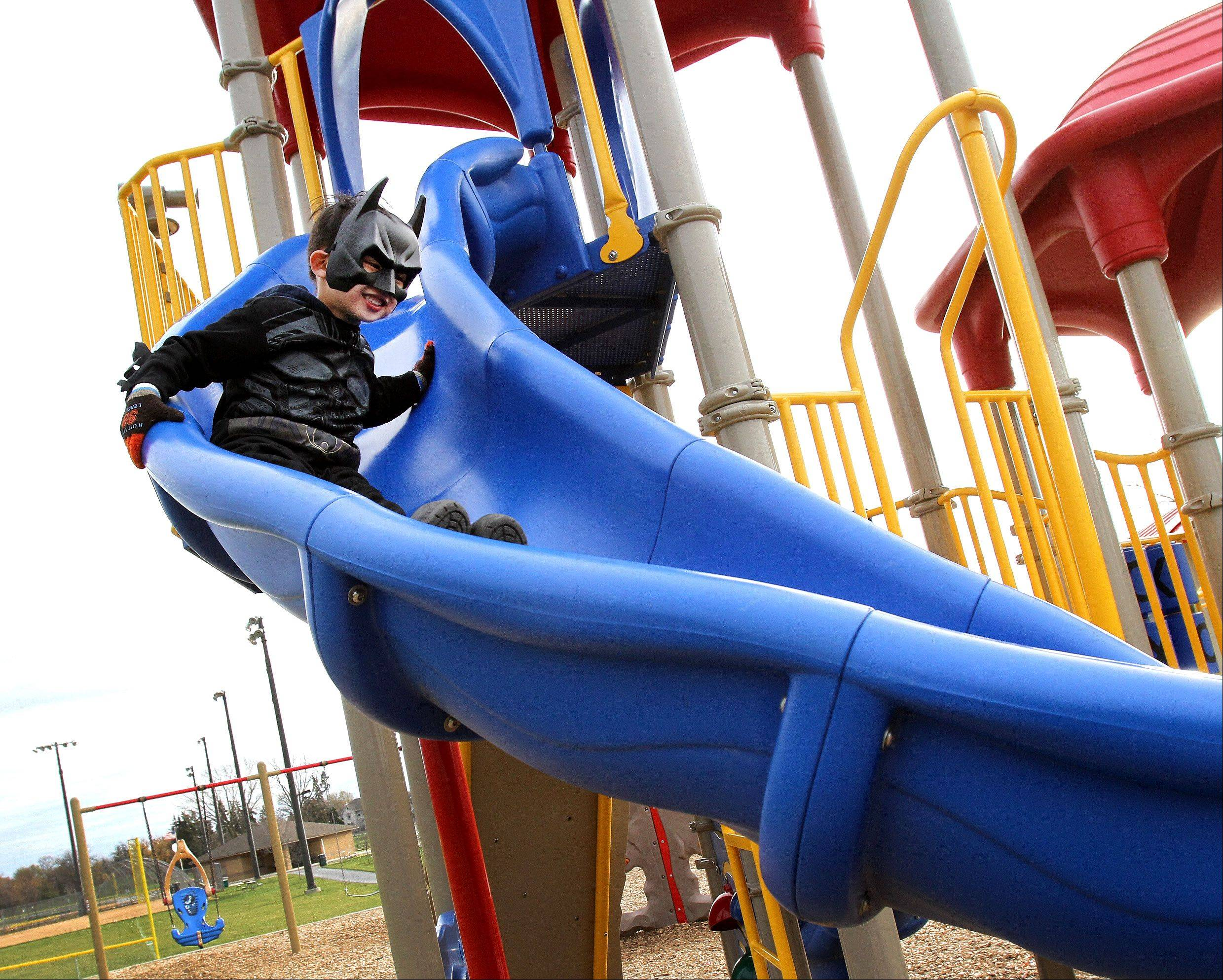 Ethan Tseng, 4, of Roselle, dressed as Batman, test out the new playground outside the Clauss Recreation Center in Roselle Tuesday during its grand opening.