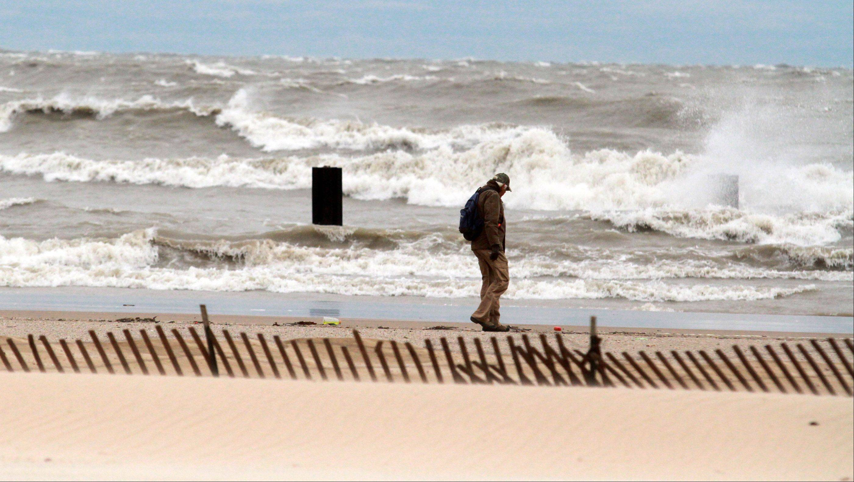 A man walks the beach line of Lake Michigan as waves battle the shoreline at North Avenue Beach in Chicago on Tuesday, October 30.