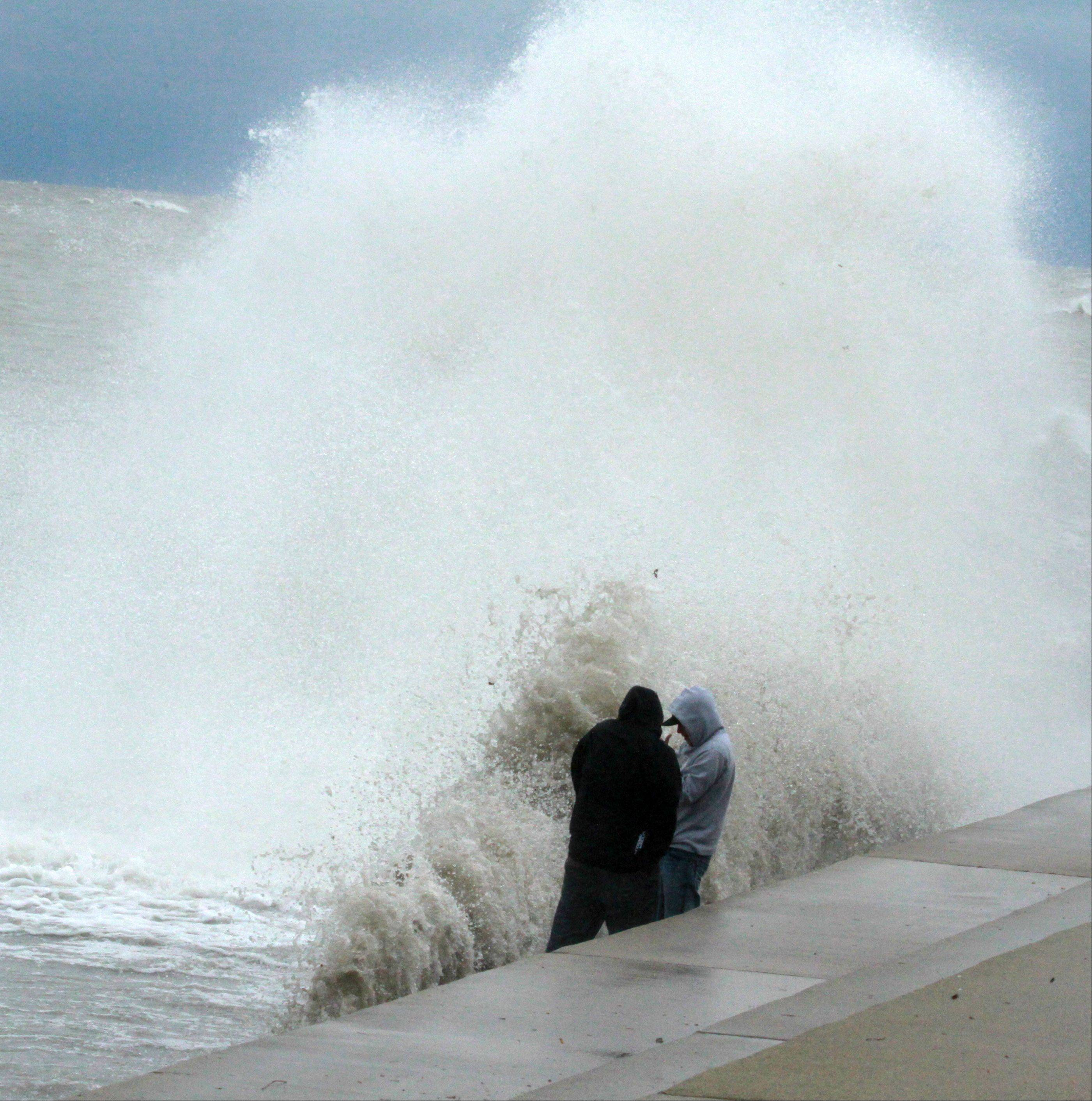 Mitch Mayle of North Riverside and Joe Krejci of La Grange Park are overtaken by a giant wave as they take pictures near Sydney R. Marovitz Golf Course on Lake Michigan shoreline in Chicago on Tuesday, October 30.