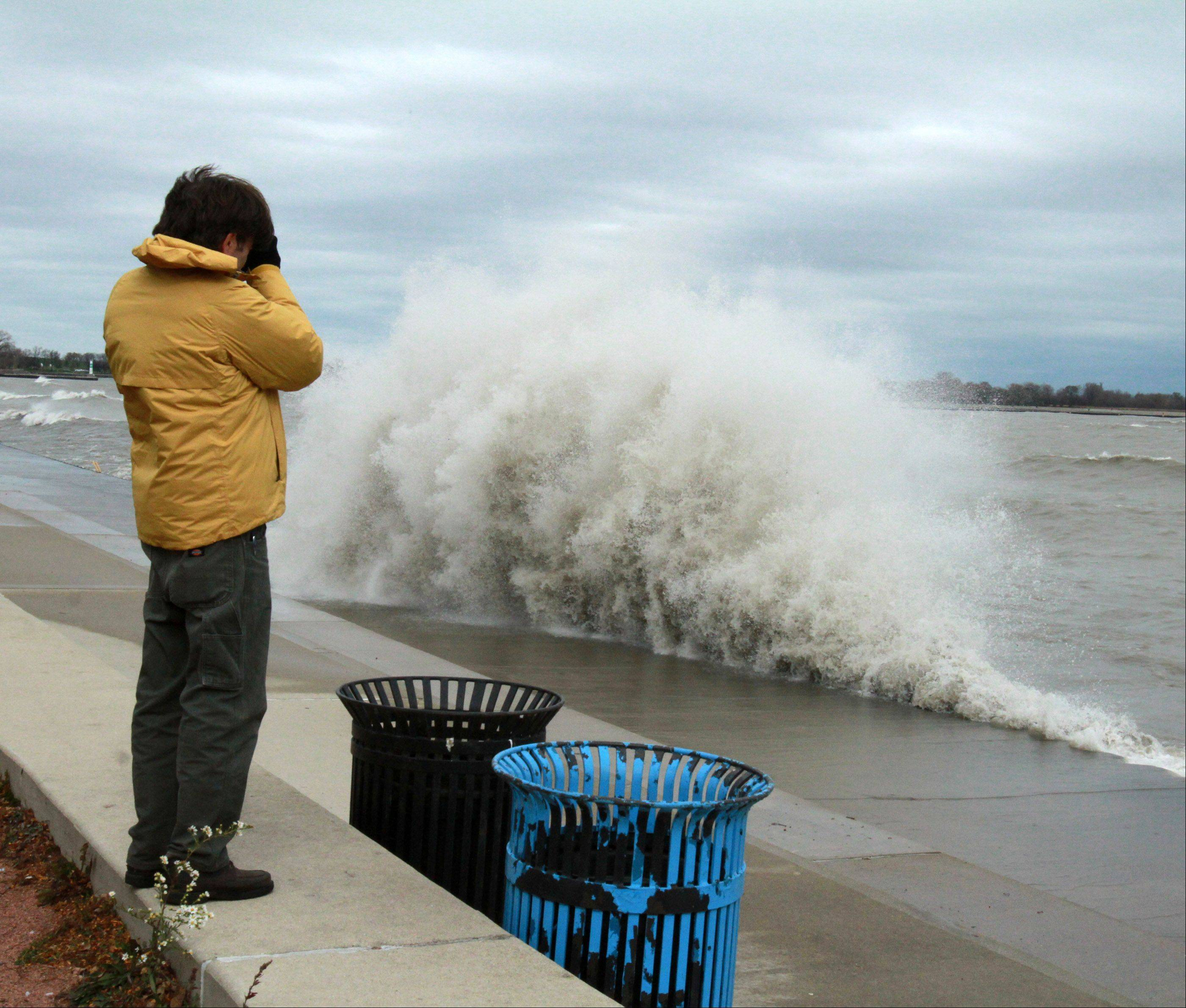 A photographer takes pictures near Sydney R. Marovitz Golf Course as giant waves batter Lake Michigan shoreline in Chicago on Tuesday, October 30.