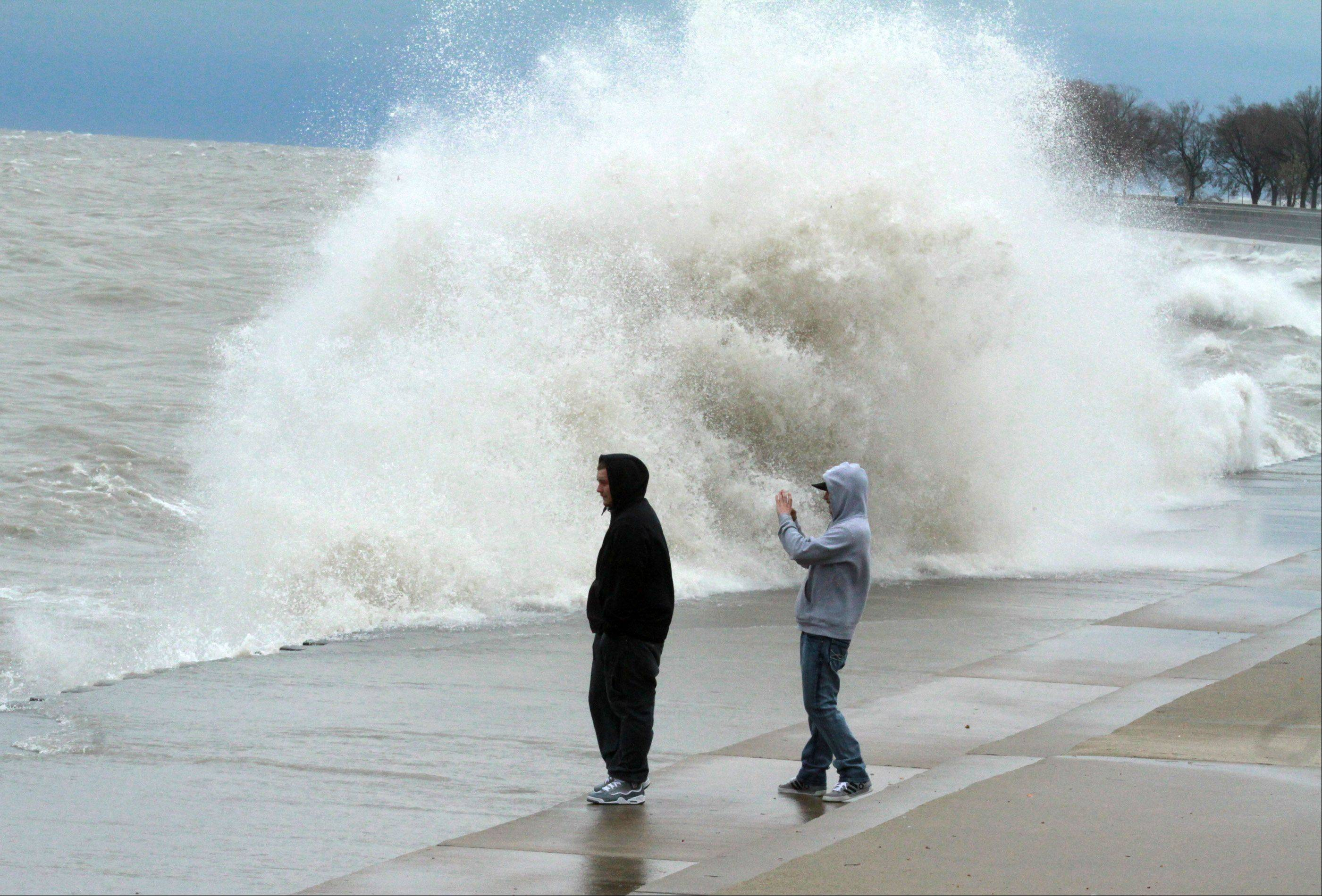 Mitch Mayle of North Riverside and Joe Krejci of La Grange Park take pictures near Sydney R. Marovitz Golf Course as giant waves batter Lake Michigan shoreline in Chicago on Tuesday, October 30.