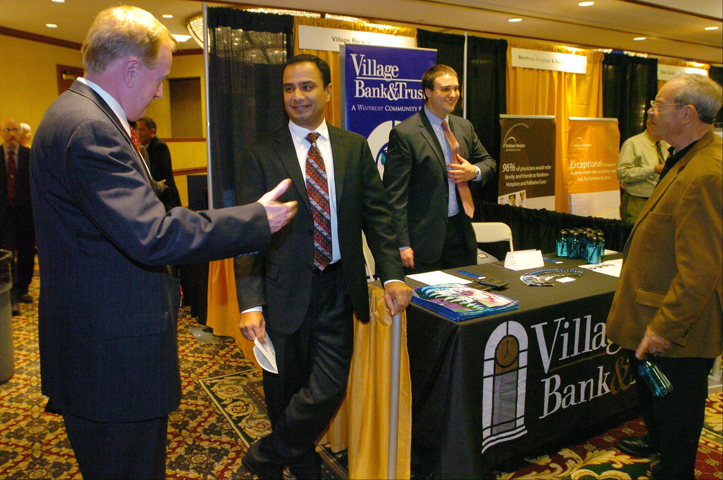 James Gillis and Syed Hussaini of Village Bank & Trust talk business by their booth.
