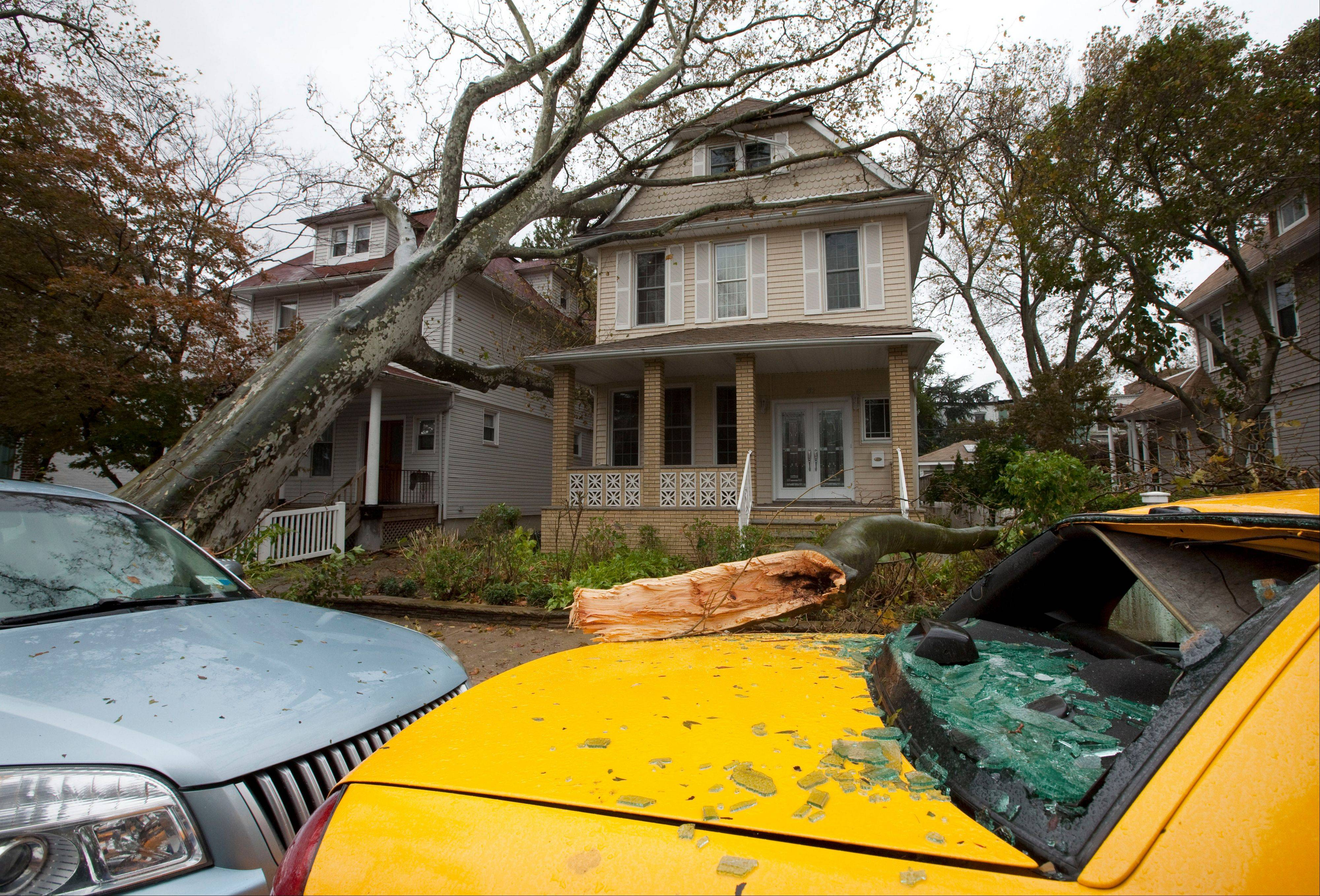 A tree leans against a house Tuesday, Oct. 30, 2012, in the Bay Ridge neighborhood in the Brooklyn borough of New York, while another tree lies on a taxi with a shattered rear window in the aftermath of superstorm Sandy. New York City awakened Tuesday to a flooded subway system, shuttered financial markets and hundreds of thousands of people without power a day after a wall of seawater and high winds slammed into the city, destroying buildings and flooding tunnels.