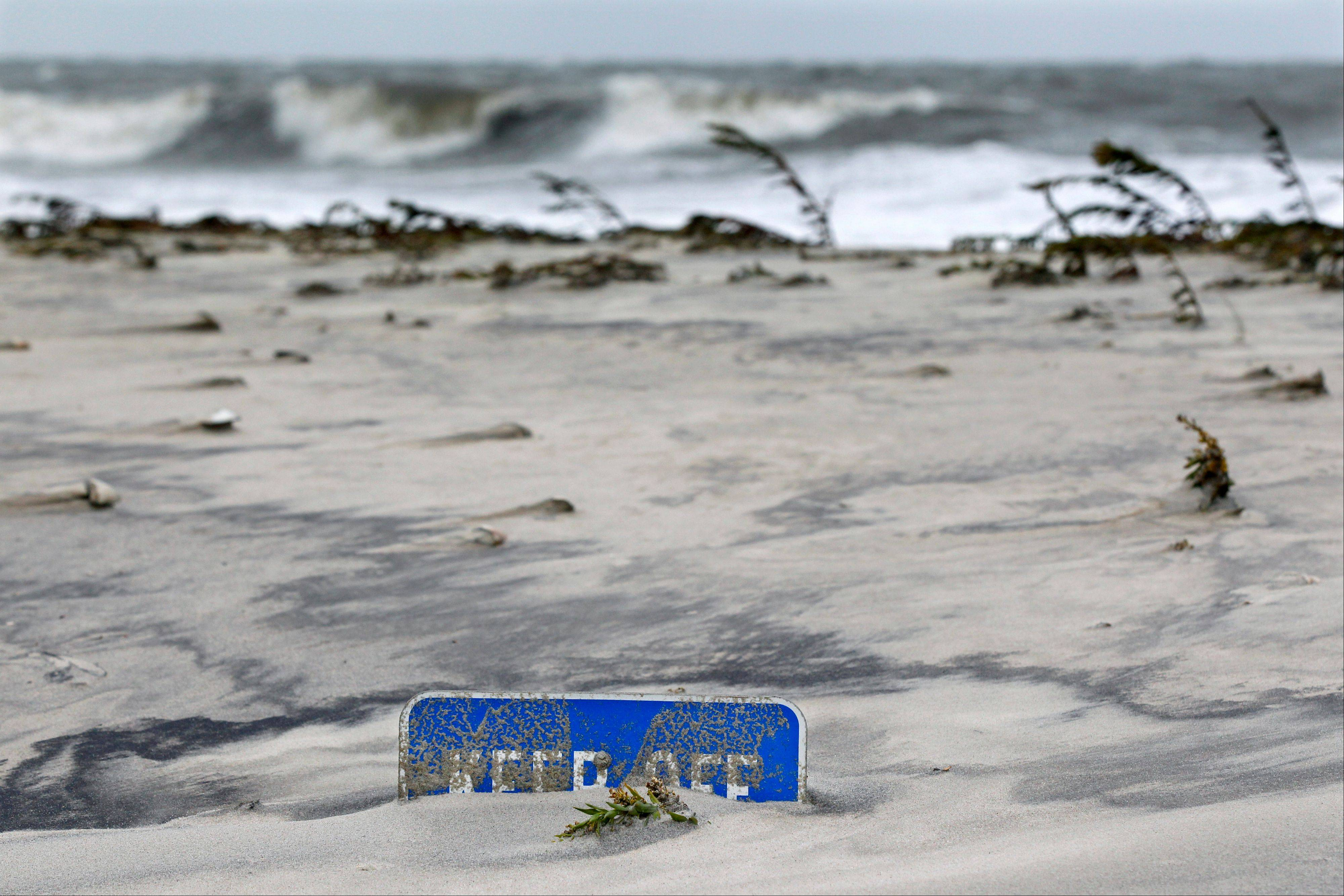 A keep off the dunes sign is buried Tuesday morning, Oct. 29, 2012, in Cape May, N.J., after a storm surge from superstormSandy pushed the Atlantic Ocean over the beach and into the streets. The storm that made landfall in New Jersey on Monday evening with 80 mph sustained winds killed at least 16 people in seven states, cut power to more than 7.4 million homes and businesses from the Carolinas to Ohio, caused scares at two nuclear power plants and stopped the presidential campaign cold.