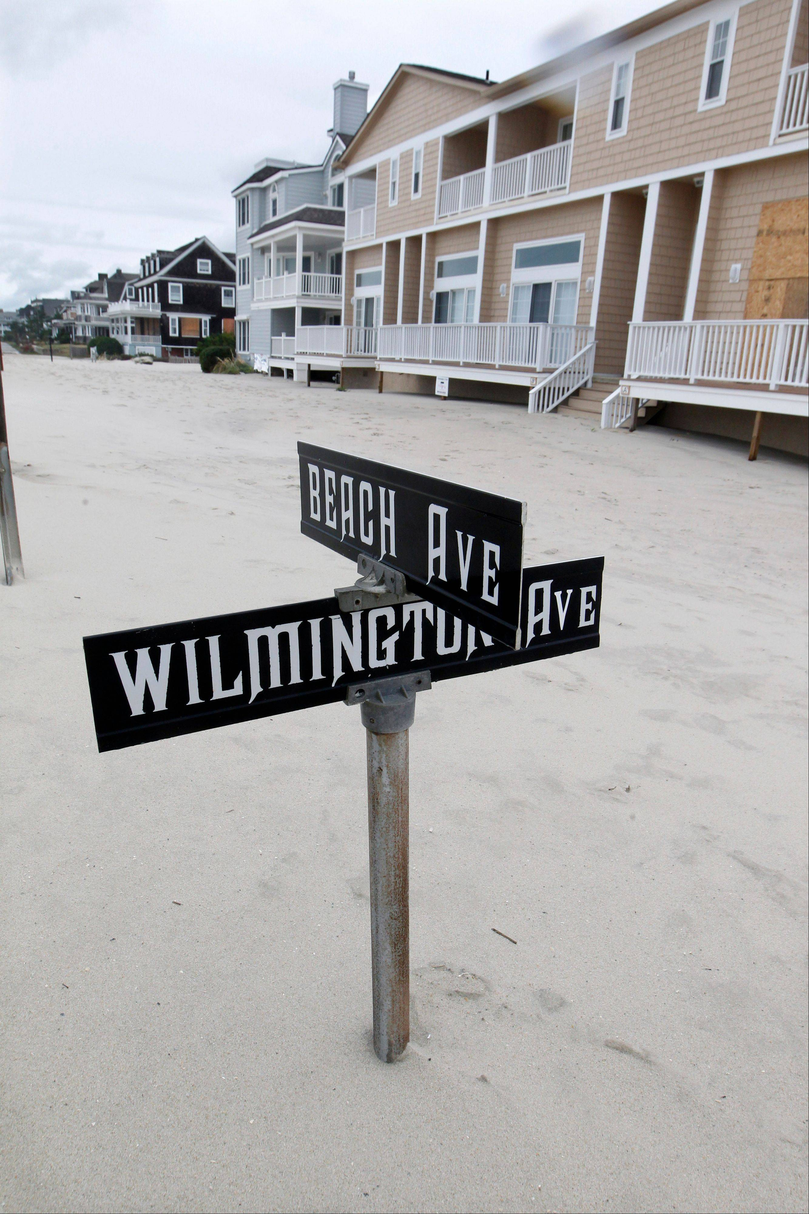 A street sign is partially buried in sand Tuesday morning, Oct. 30, 2012, in Cape May, N.J., after a storm surge from Sandy pushed the Atlantic Ocean over the beach and across Beach Avenue.